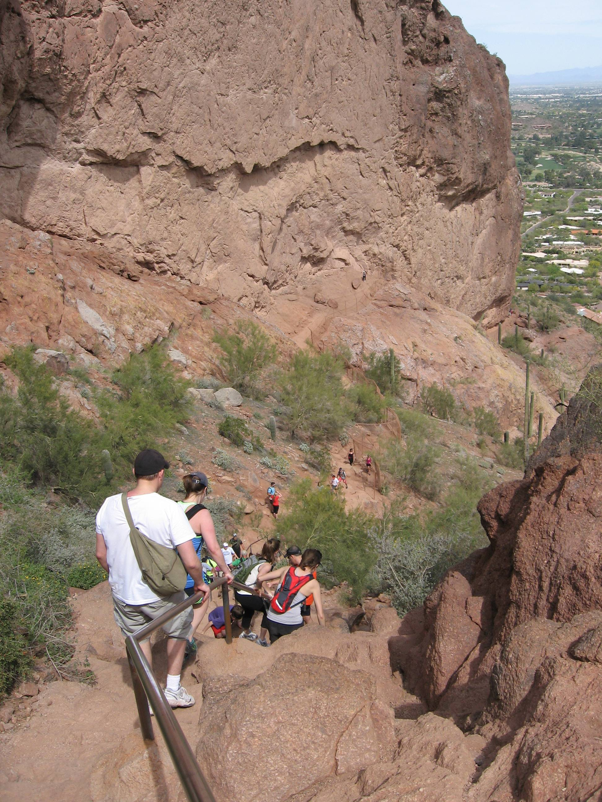 Visitors descend a steep portion of the Camelback Mountain trail in Phoenix, Ariz. The 2,704-foot-high mountain offers 360-degree views of distant mountain ranges and closer views of golf courses and pools, all framed by tall saguaros and blooming wildflowers.
