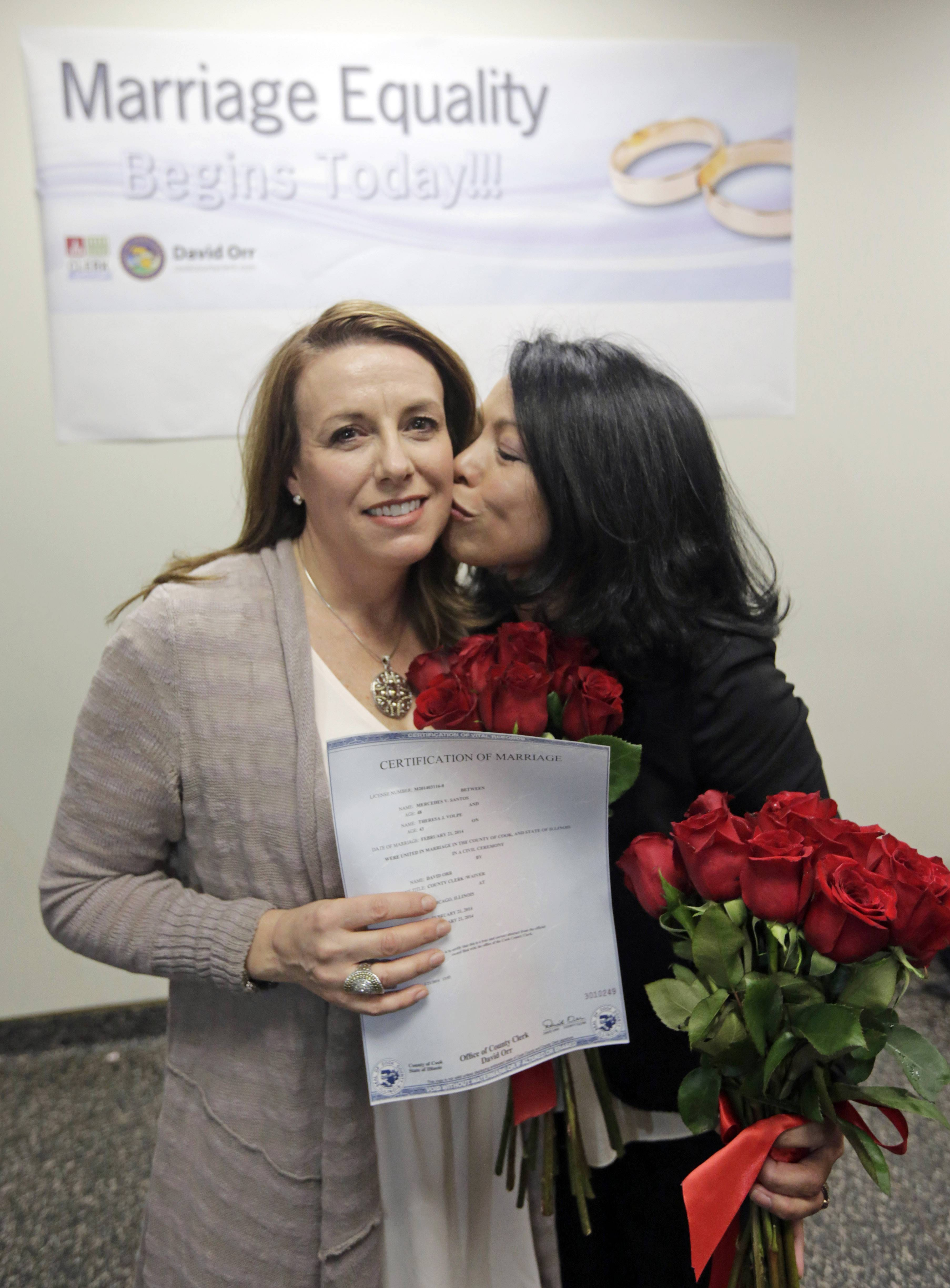 Theresa Volpe, left, and Mercedes Santos show off their marriage certificate after being married in Cook County in February. Other Chicago-area counties start offering same-sex marriage licenses Monday.