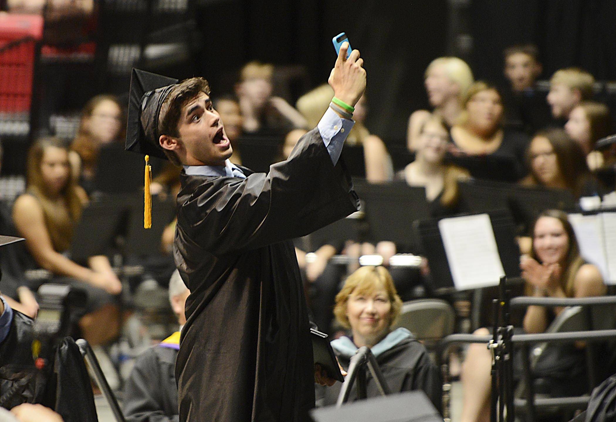 Graduate Dylan Snodgrass pauses for a selfie onstage after receiving his diploma at the Kaneland High School 2014 commencement exercises Sunday in Dekalb.