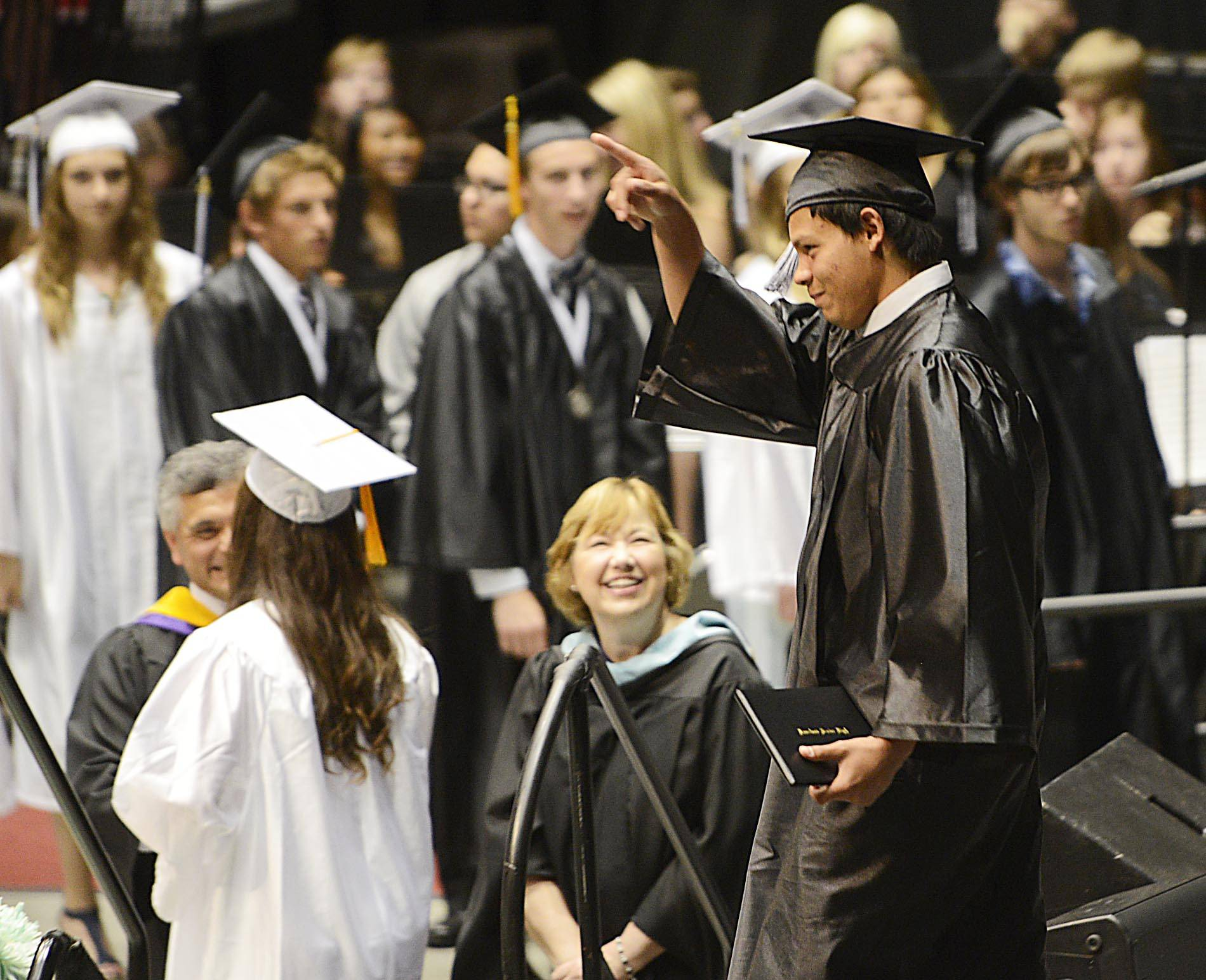 Graduate Juan Delgado points to his family after receiving his diploma at the Kaneland High School 2014 commencement exercises Sunday in Dekalb.