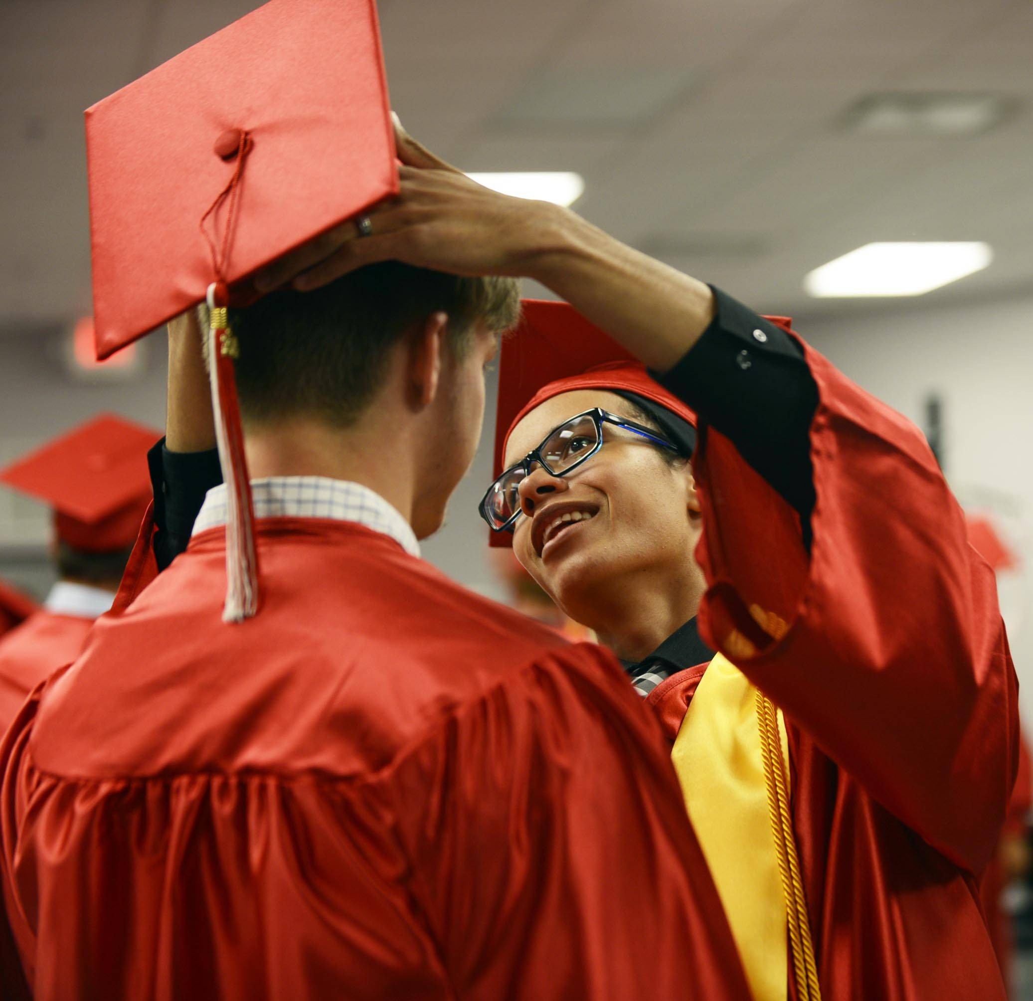 Salutatorian Cory Anderson helps a classmate with his mortarboard at the Aurora Christian High School commencement ceremony Sunday in Aurora.