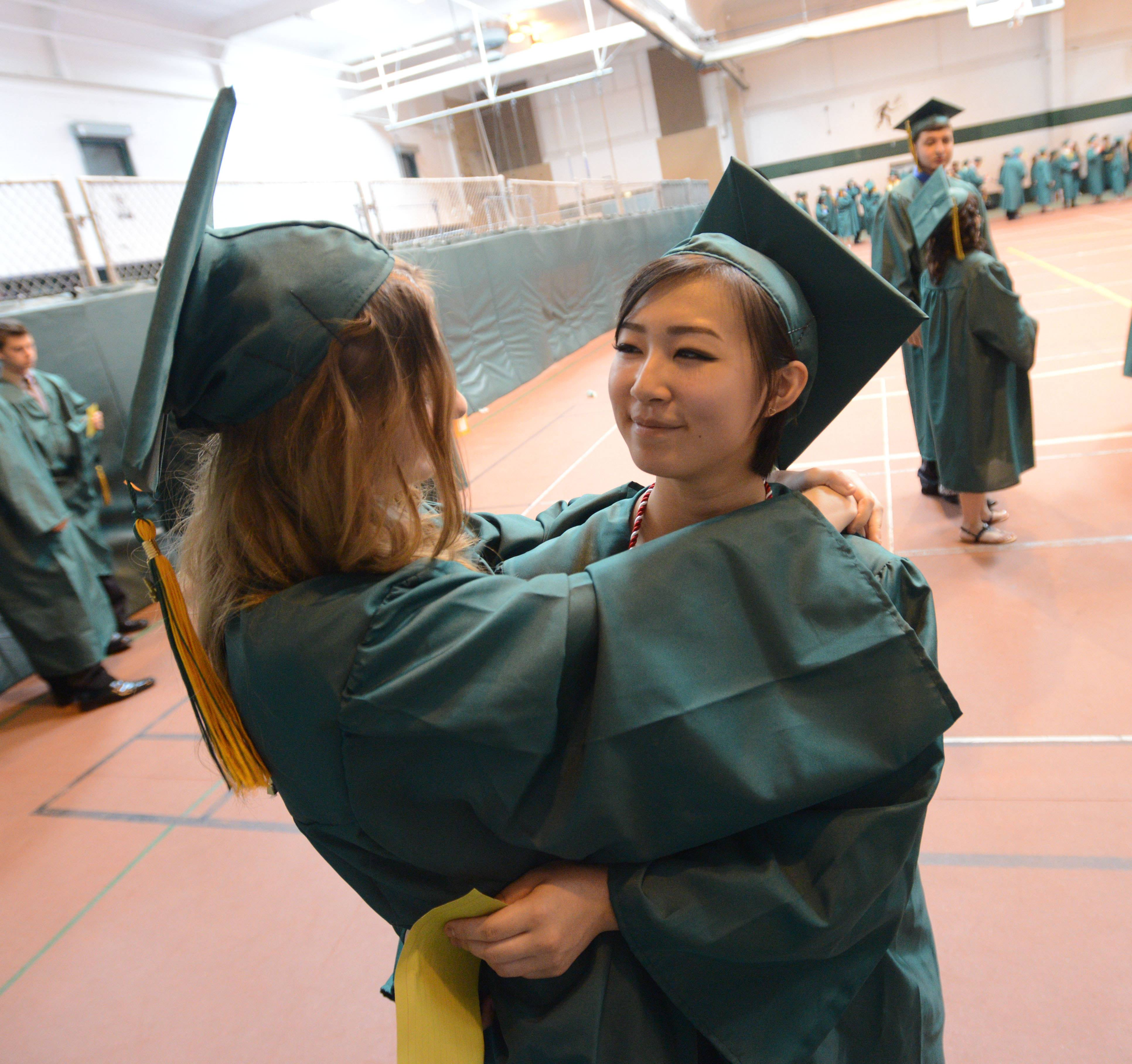 Martyna Rebielak, 18, of Elk Grove gets a hug from Aki Sato, 18, of Mount Prospect before the Elk Grove High School graduation Sunday.