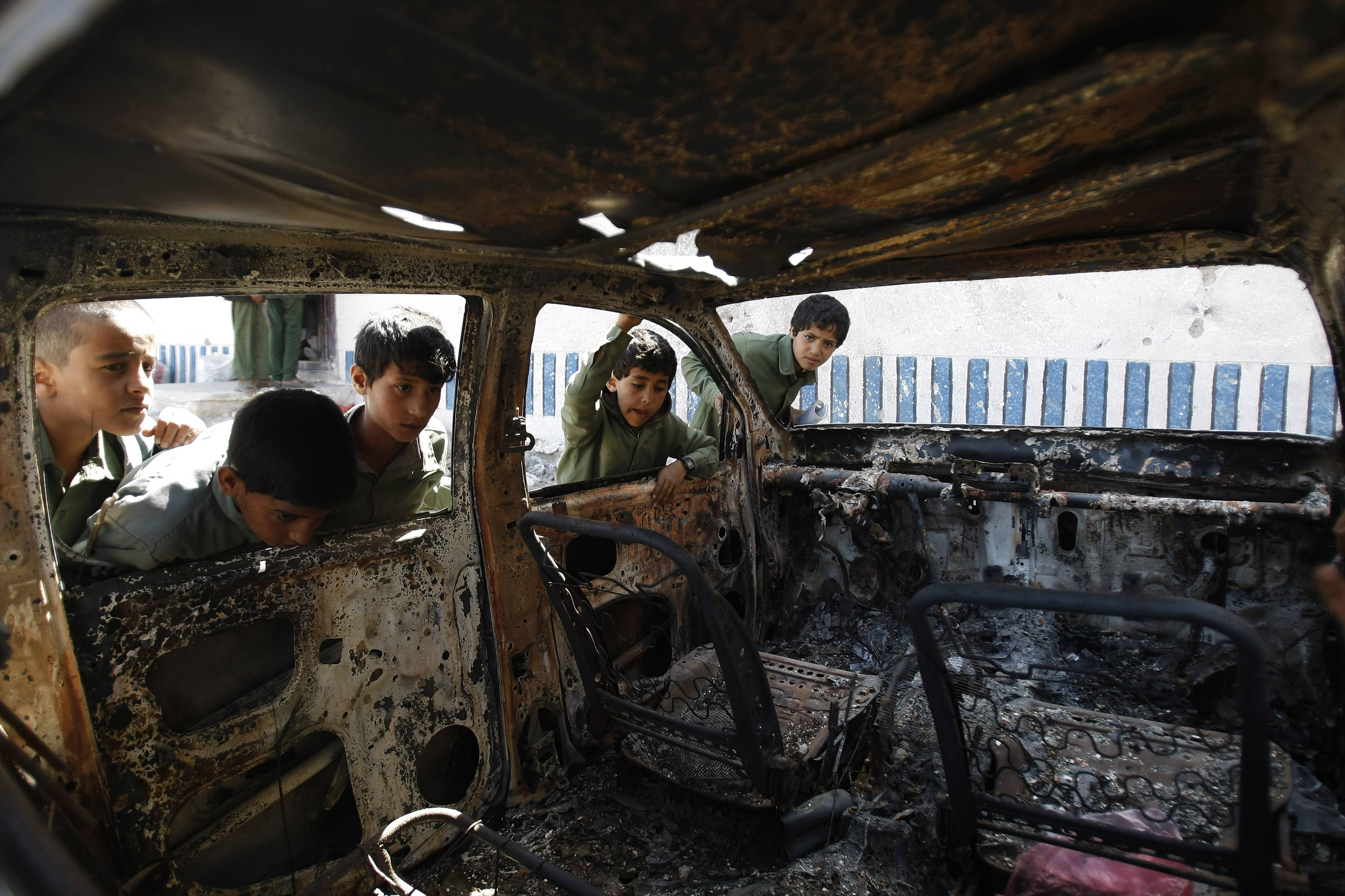 Yemeni boys look at a vehicle destroyed during a police raid on an al-Qaida militants' hideout in the Arhab region, north of Sanaa, Yemen, which resulted in the death of five militants and six soldiers, in this file photo from May 27.