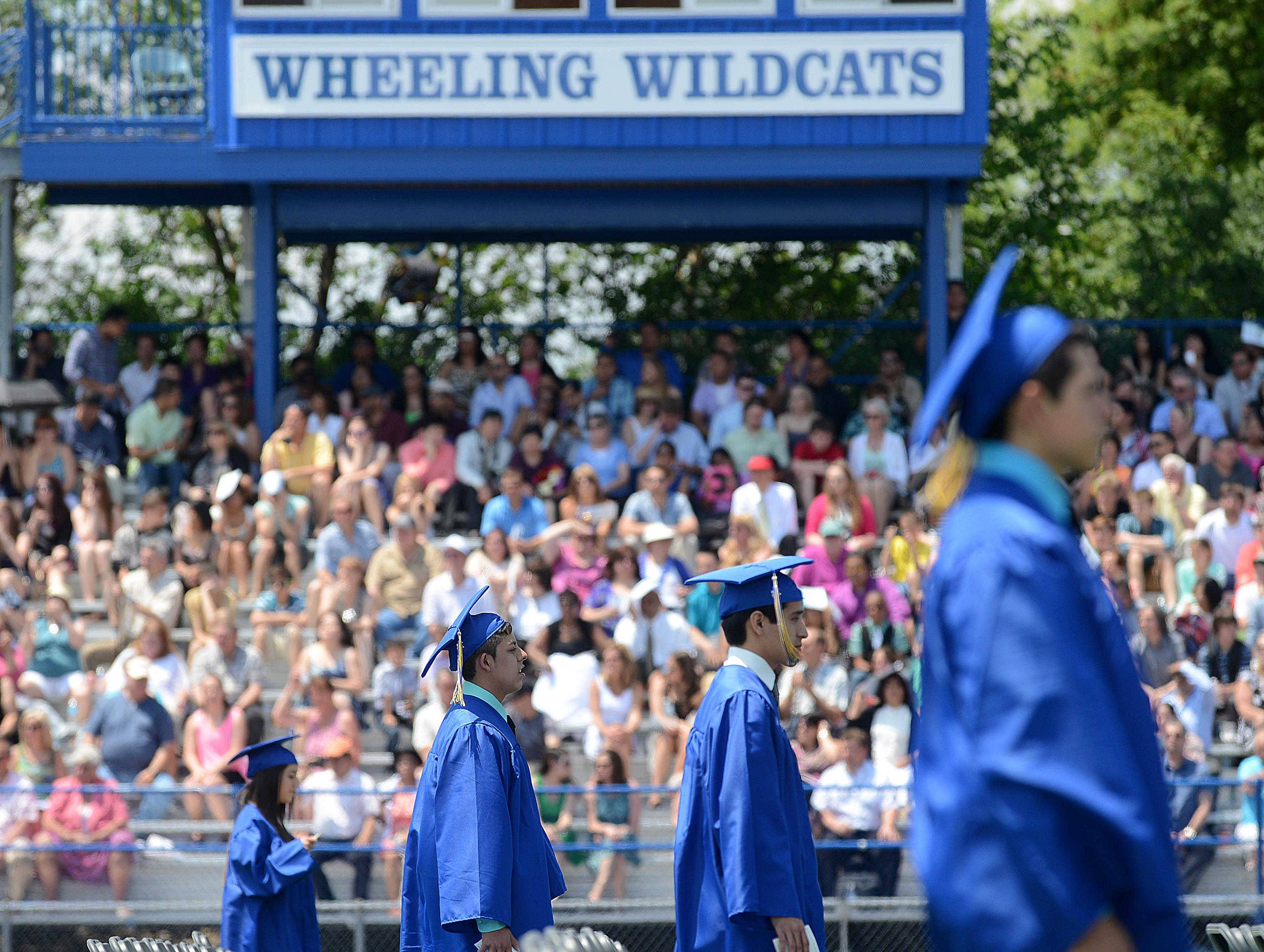 Graduates-to-be march into the 49th commencement at Wheeling High School on Sunday at the school.