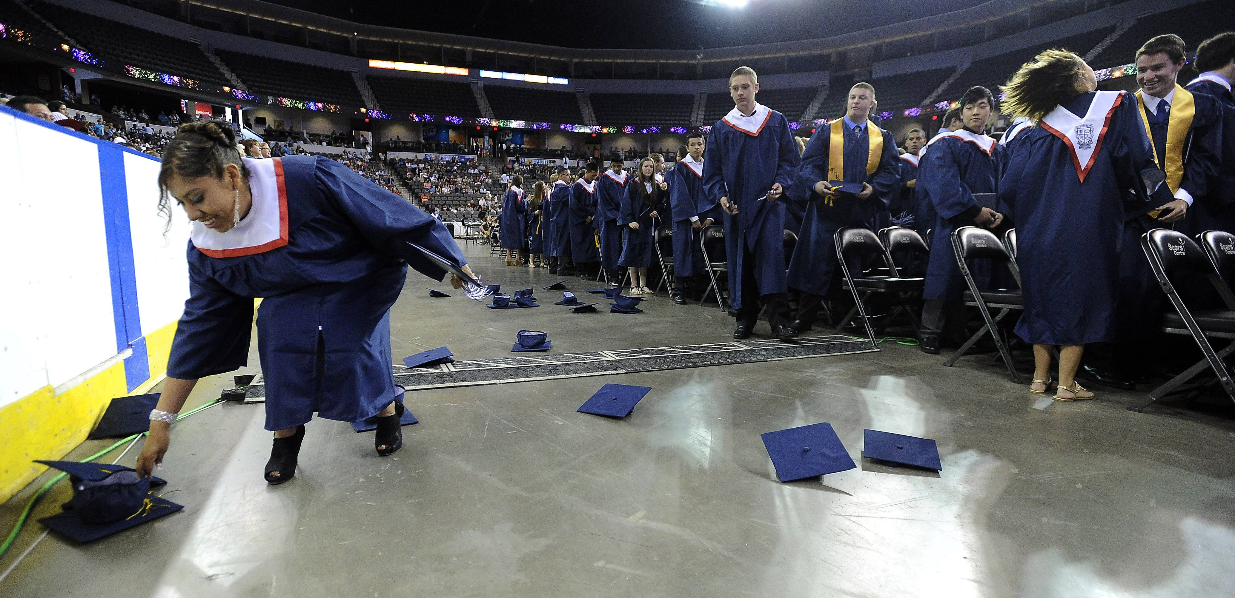 The graduation caps fly as Conant students says goodbye to their four years of high school while Michelle Juarez-Calderon looks to keep her cap as the 49th annual commencement comes to an end at the Sears Centre on Sunday.