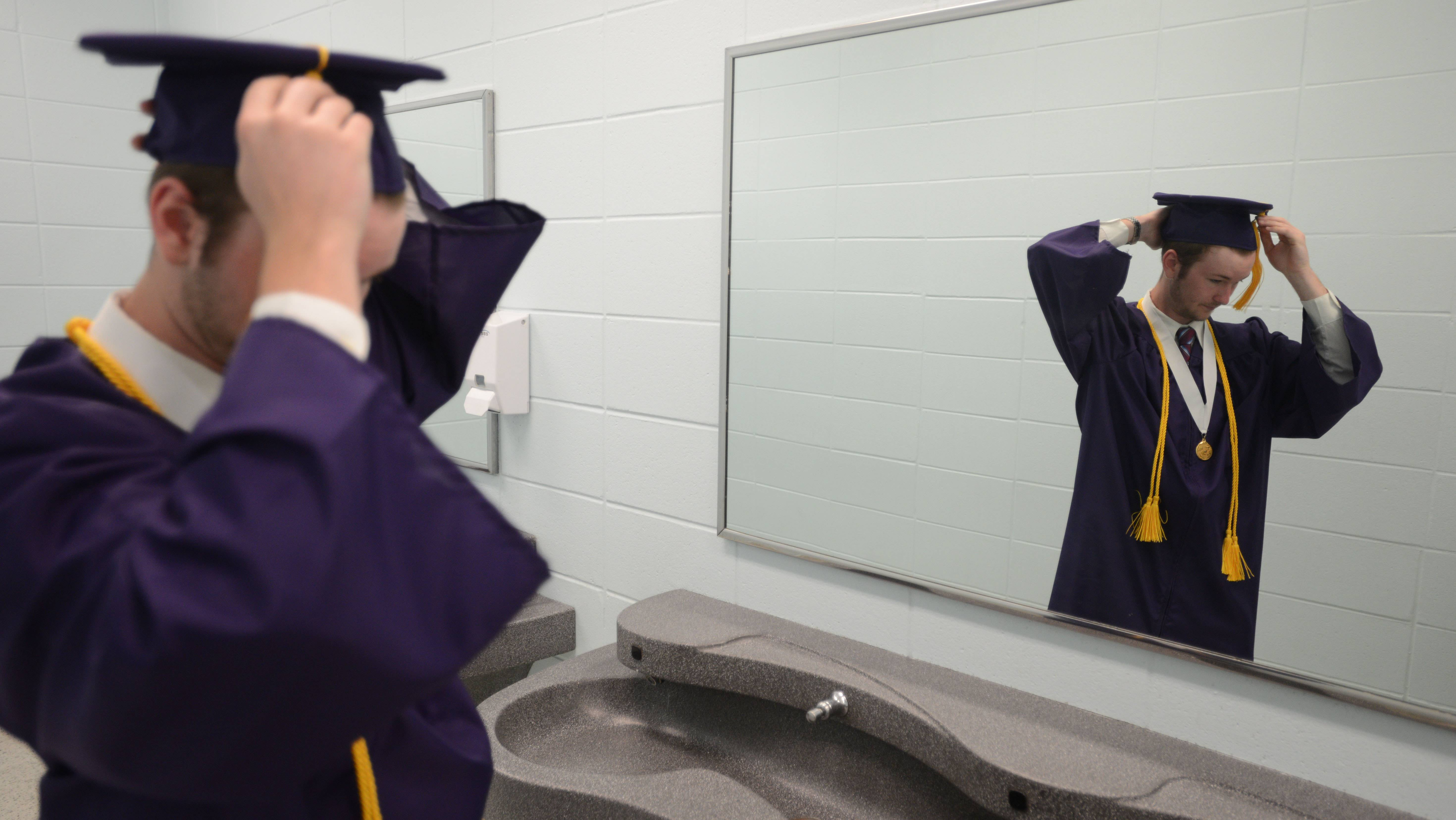 Peter Timotijevic, 18, of Arlington Heights adjusts his cap before the Rolling Meadows High School graduation Saturday.