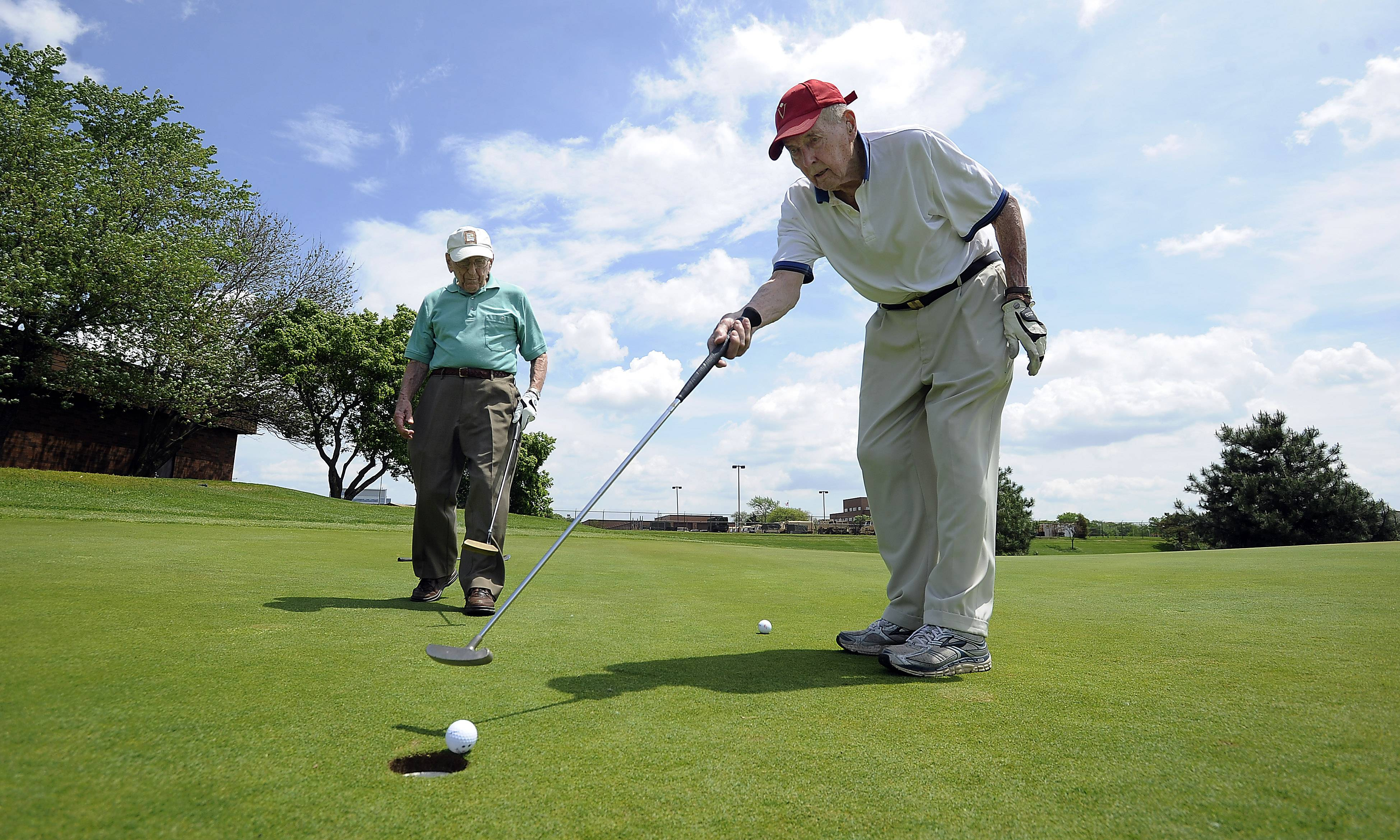 Tapping in a putt, 98-year-old Dick Breeden golfs with Dick Muhlethaler, who is 103. With a combined age of 201, the Luther Village residents are capable of scoring half their ages over nine holes in their games every Tuesday at Arlington Lakes Golf Club in Arlington Heights.