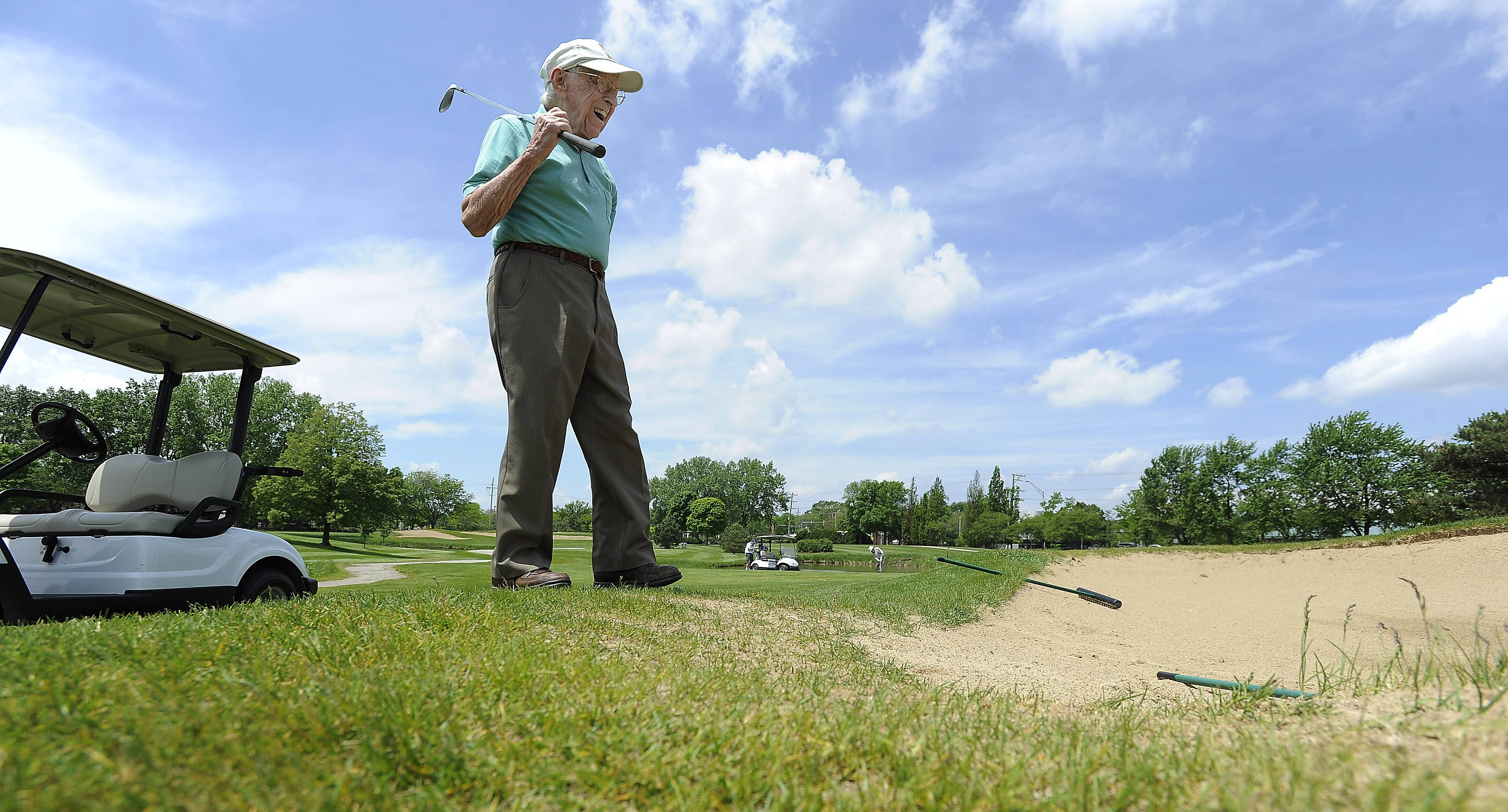 Walking down into a sand trap would be an ordeal for most centenarians, but 103-year-old golfer Dick Muhlethaler laughs as he ponders the difficult chip shot he faces on the 9th hole at Arlington Lakes Golf Club.