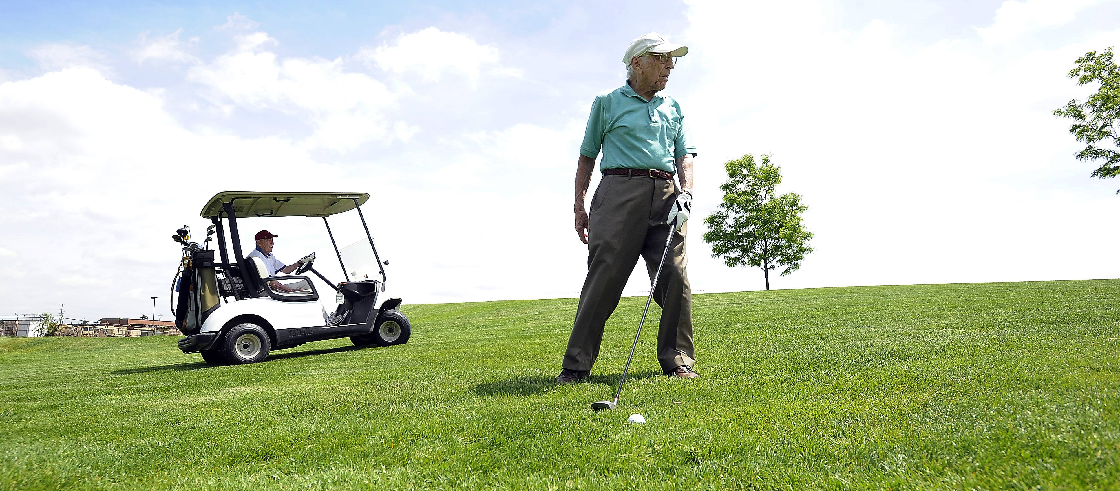 At 103 years old, golfer Dick Muhlethaler eyes the green as he ponders his next shot. Playing partner Dick Breeden, 98, waits in the golf cart.