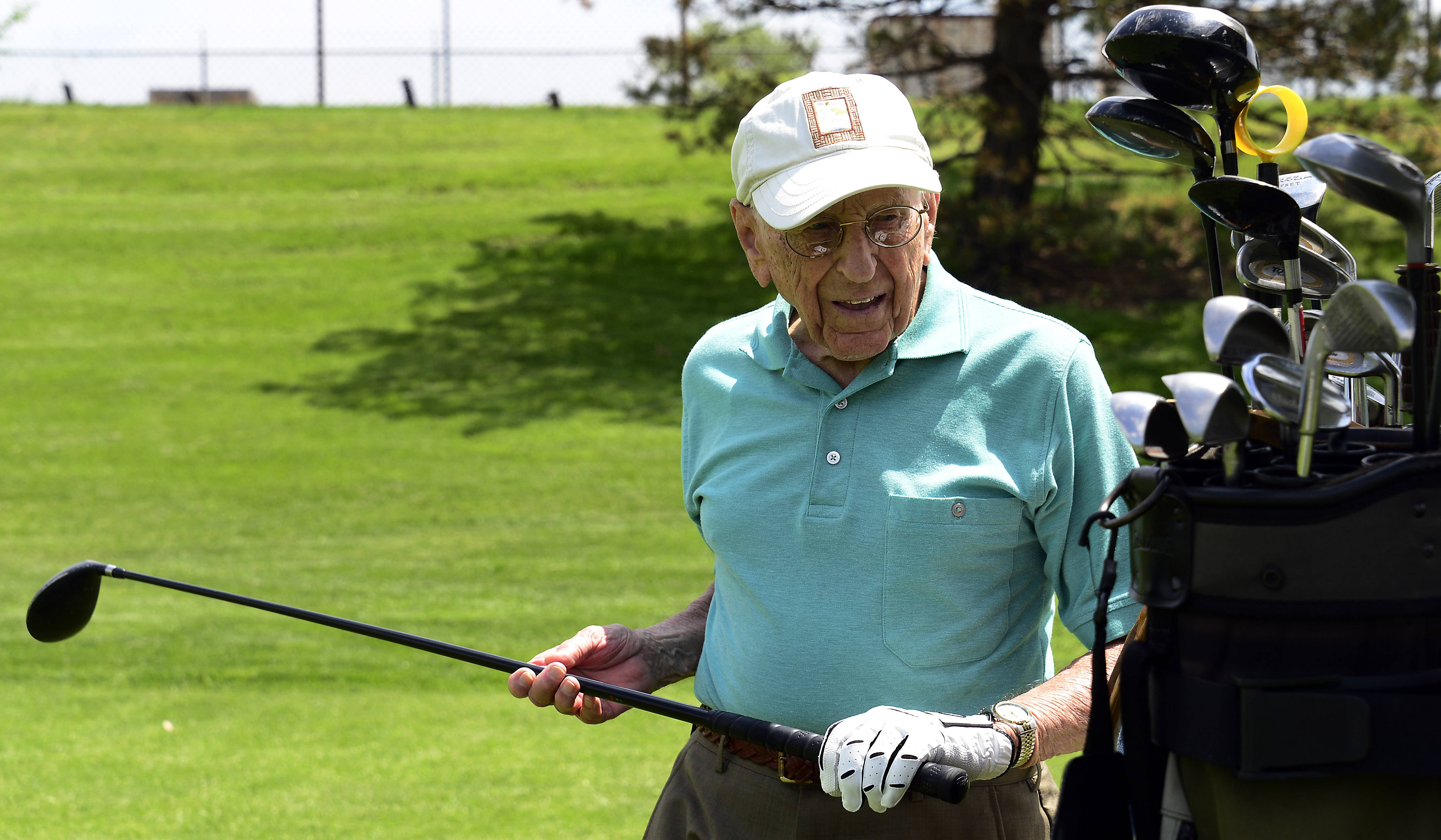 Selecting his 3-wood to tee off, golfer Dick Muhlethaler, 103, is known for having a smooth swing. His secret is a contraption that lets him take full swings all winter long in his Luther Village apartment in Arlington Heights.
