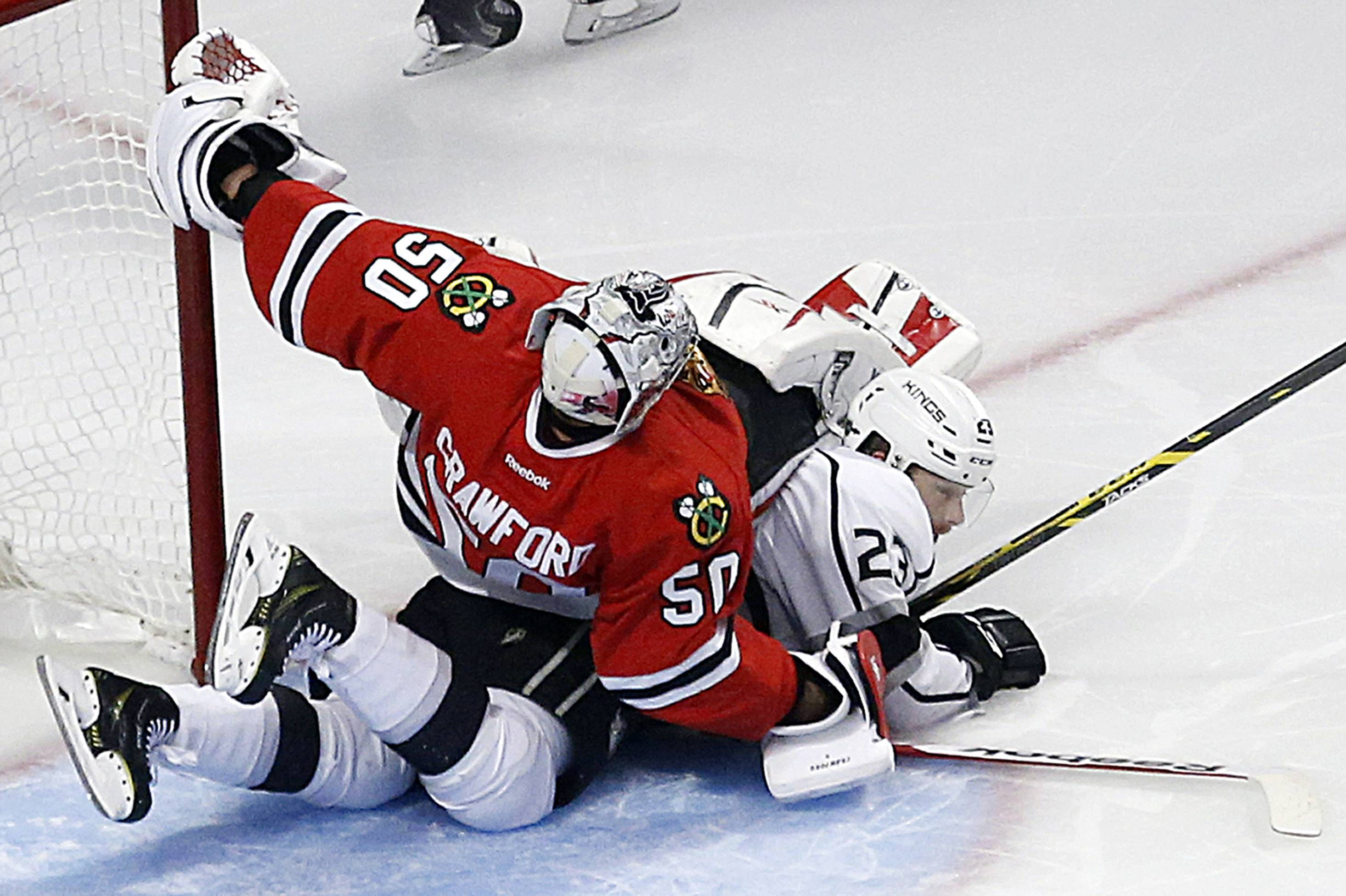 Corey Crawford collides with Dustin Brown during the second period in Game 7 of the Western Conference finals Sunday.