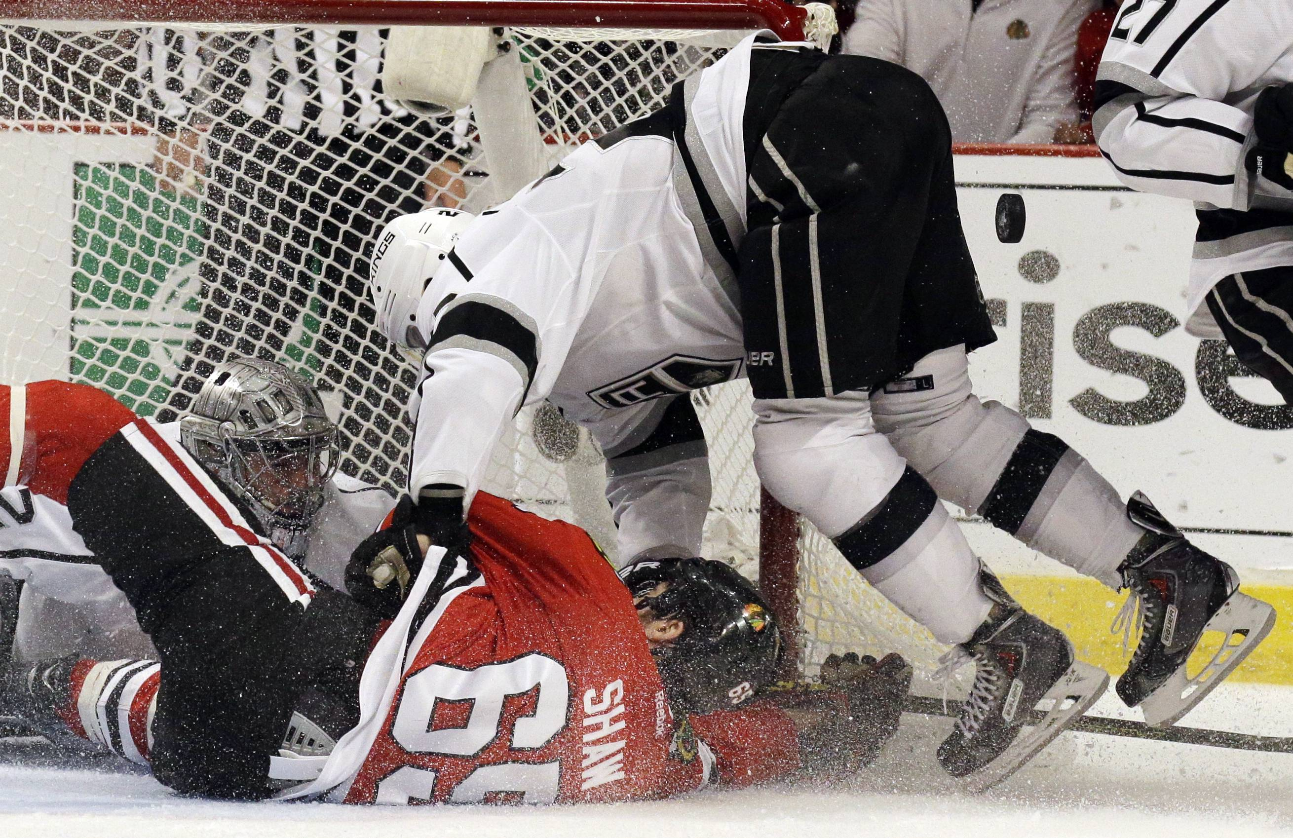 Blackhawks center Andrew Shaw (65) and Los Angeles Kings center Trevor Lewis (22) collide as Los Angeles Kings goalie Jonathan Quick (32) saves a goal  during the second period in Game 7 of the Western Conference finals in the NHL hockey Stanley Cup playoffs Sunday, June 1, 2014, in Chicago.