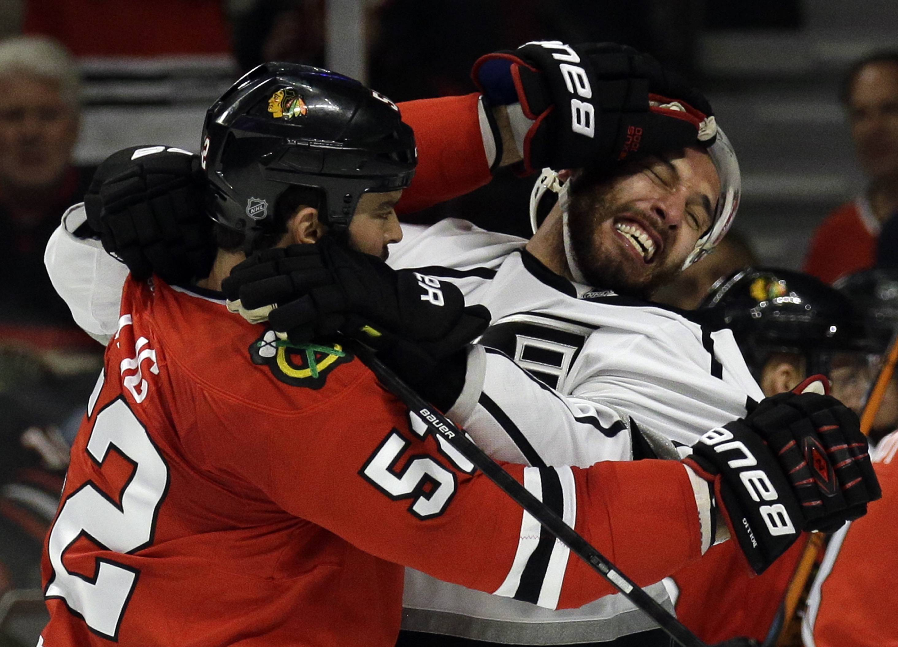 Chicago Blackhawks left wing Brandon Bollig (52) and Los Angeles Kings left wing Dwight King (74) fight during the first period.