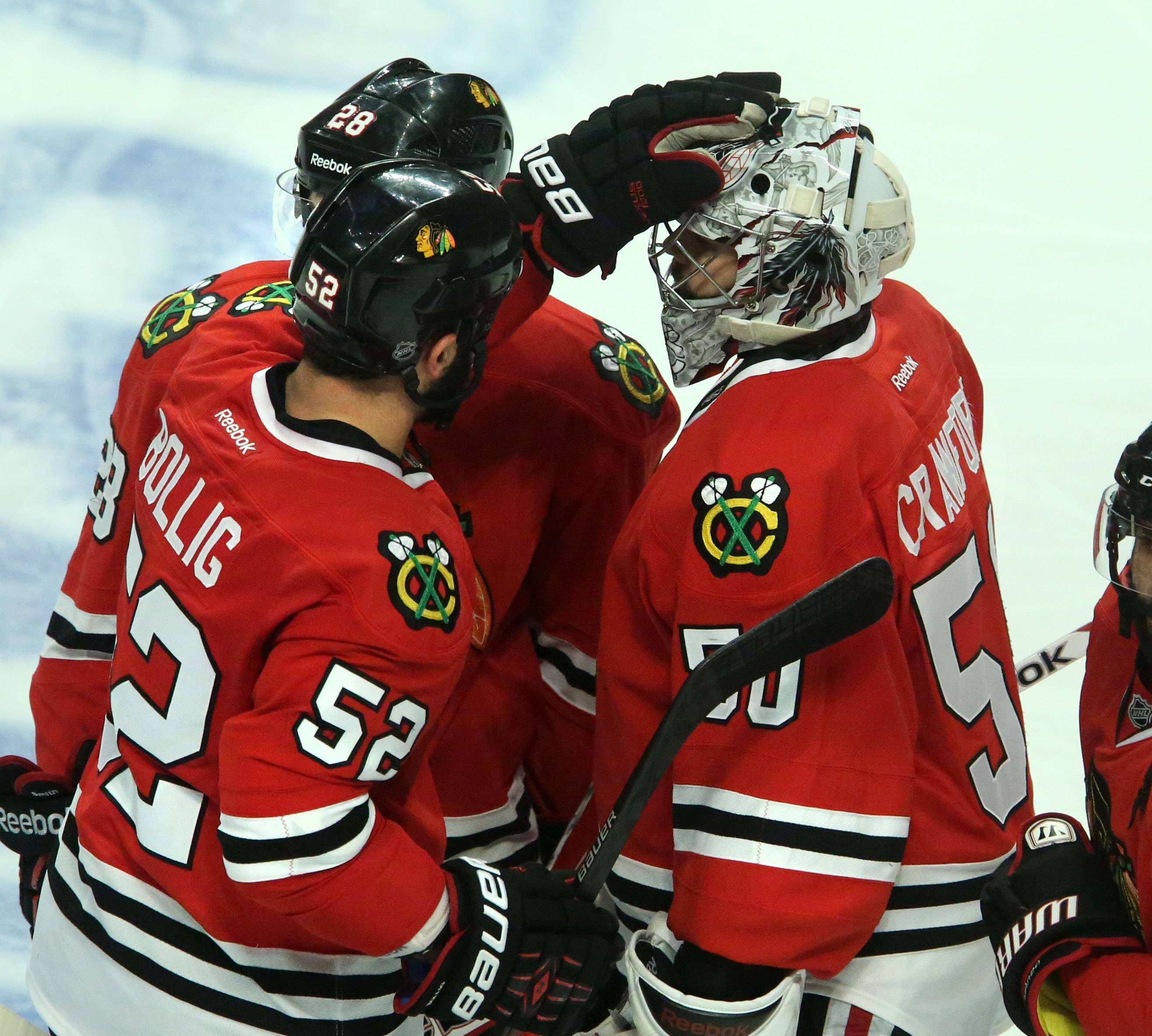 Chicago Blackhawks goalie Corey Crawford gets a hand from Brandon Bollig after letting the winning goal past him in overtime of Game 7 as the Los Angeles Kings win the Western Conference final 5-4 on Sunday at the United Center in Chicago.