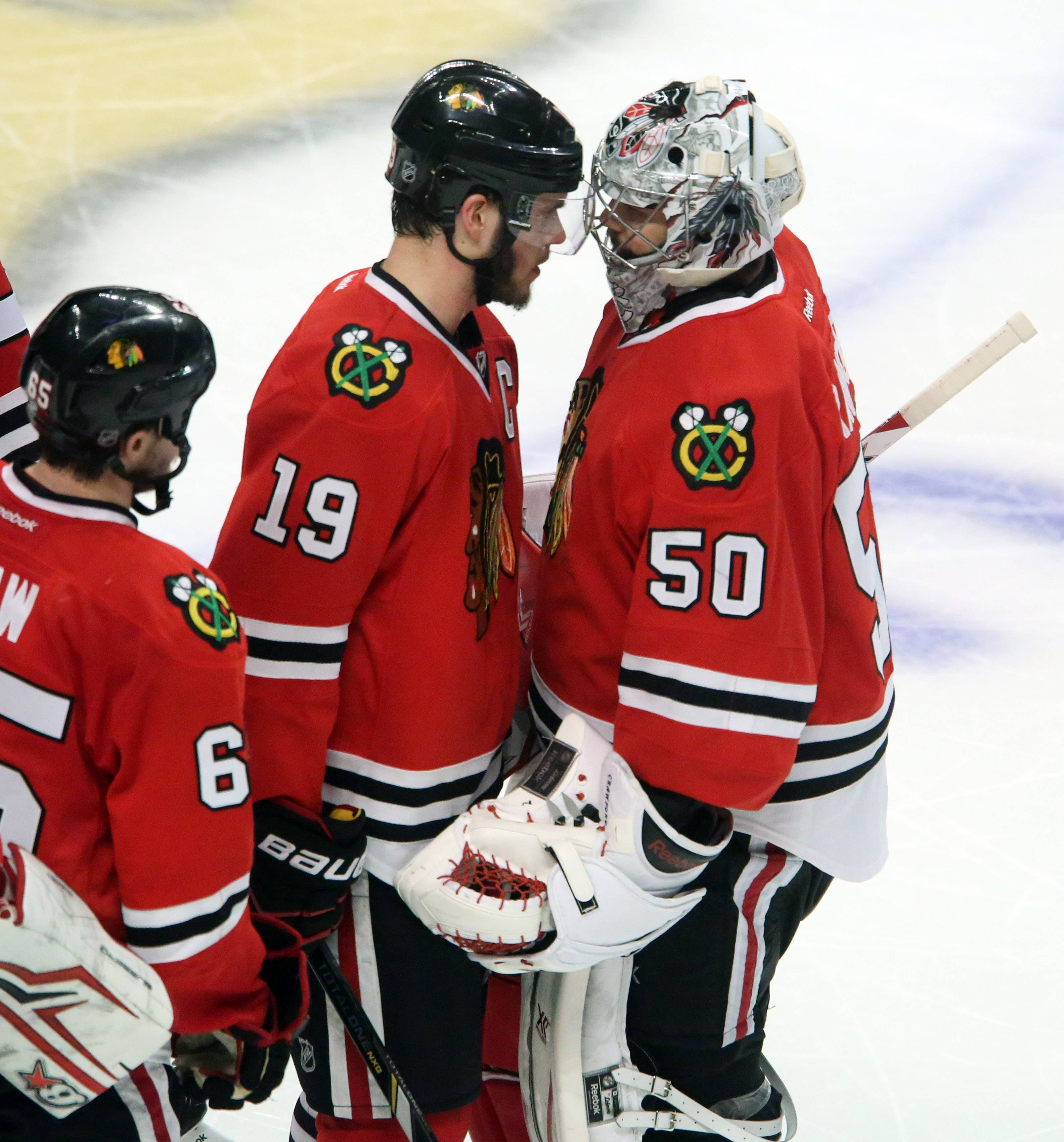 Chicago Blackhawks goalie Corey Crawford gets a hand from Jonathan Toews after letting the winning goal past him in overtime of Game 7 as the Los Angeles Kings win the Western Conference final 5-4.
