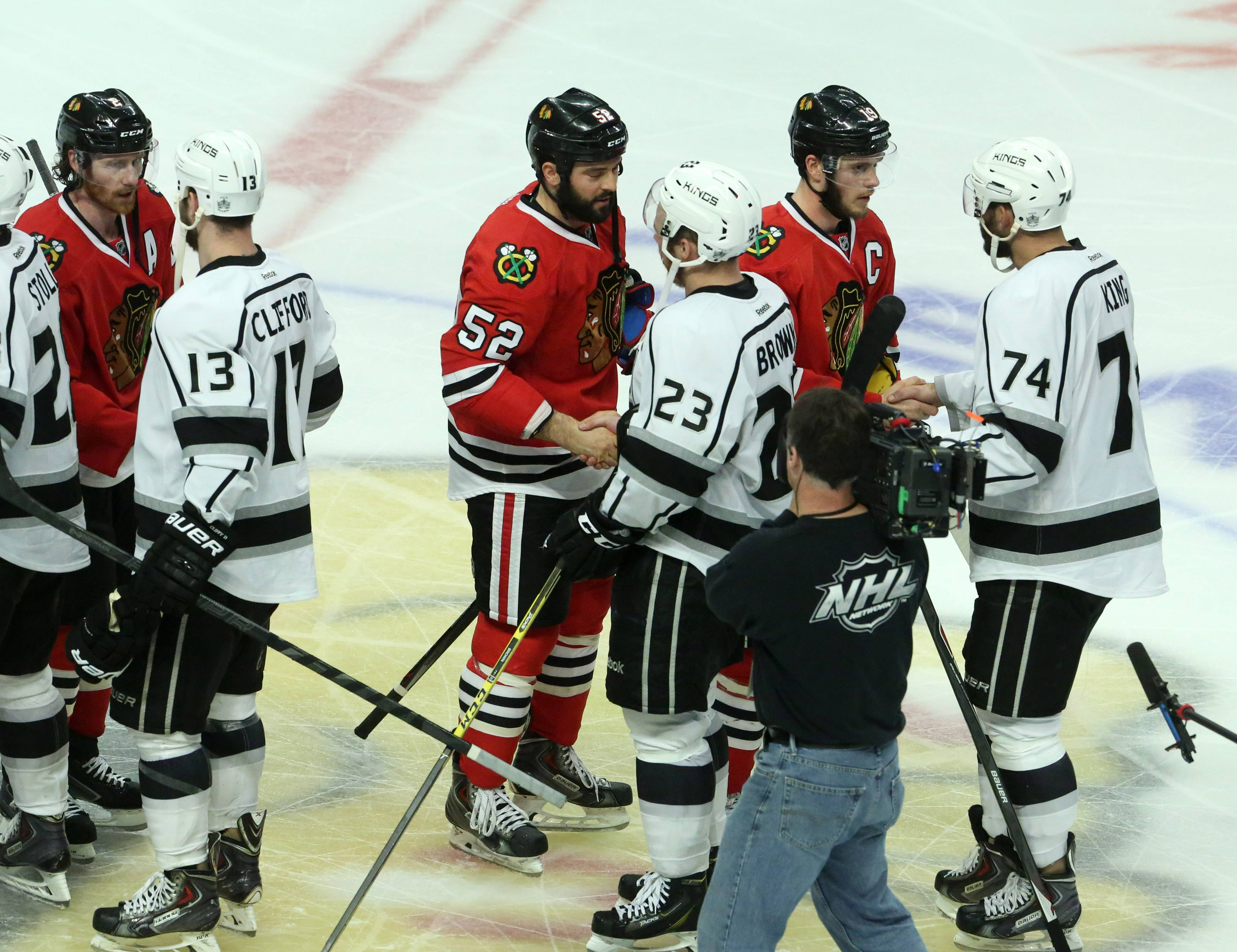 George LeClaire/gleclaire@dailyherald.com Chicago Blackhawks center Jonathan Toews shakes the hand of Los Angeles Kings left wing Dwight King and  Brandon Bollig shakes the hand of Kings right wing Dustin Brown after Game 7 of the Western Conference final.