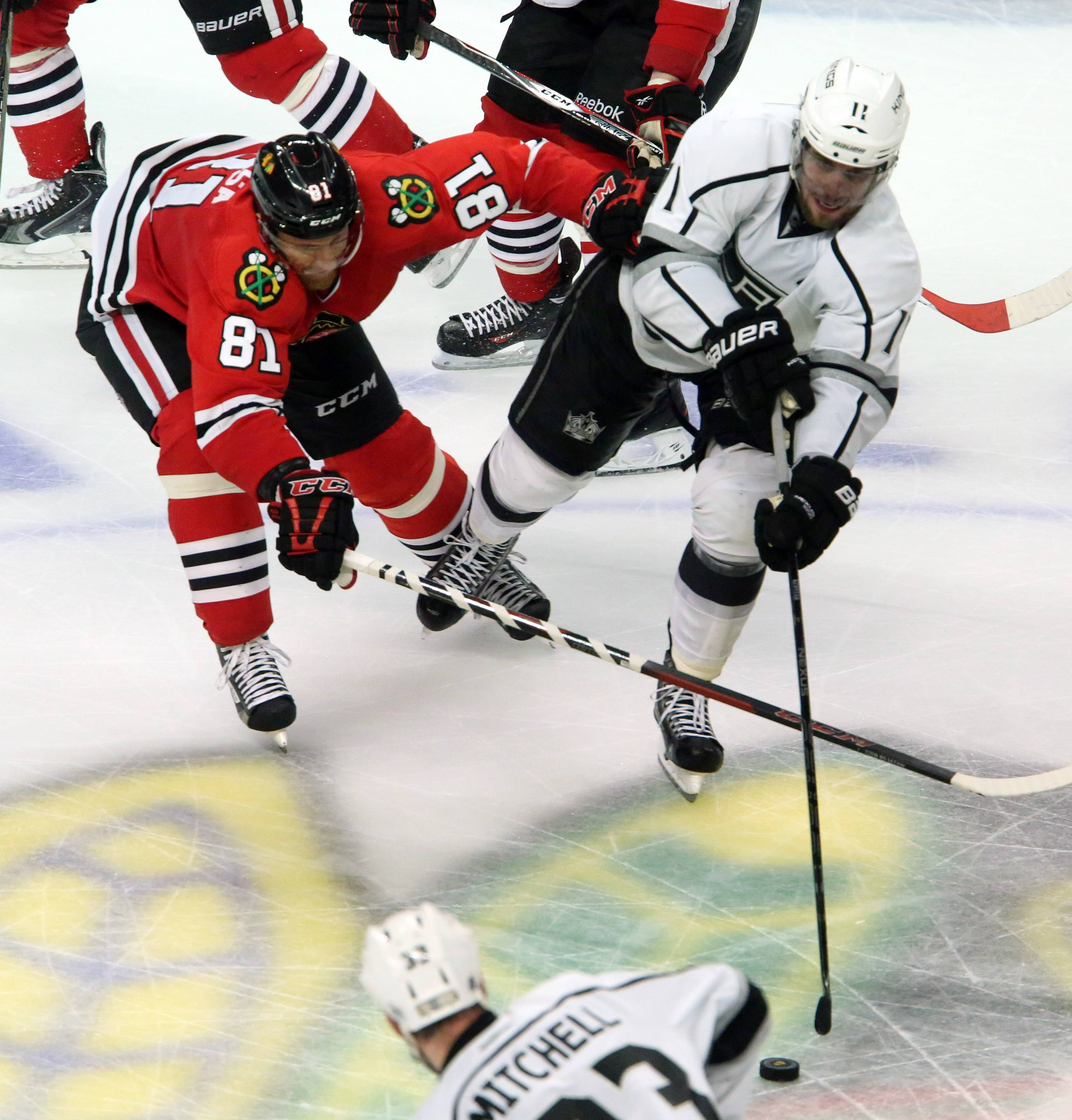 George LeClaire/gleclaire@dailyherald.com Chicago Blackhawks right wing Marian Hossa and Los Angeles Kings center Anze Kopitar race to a loose puck in the third period of Game 7 of the Western Conference finals Sunday at the United Center in Chicago.