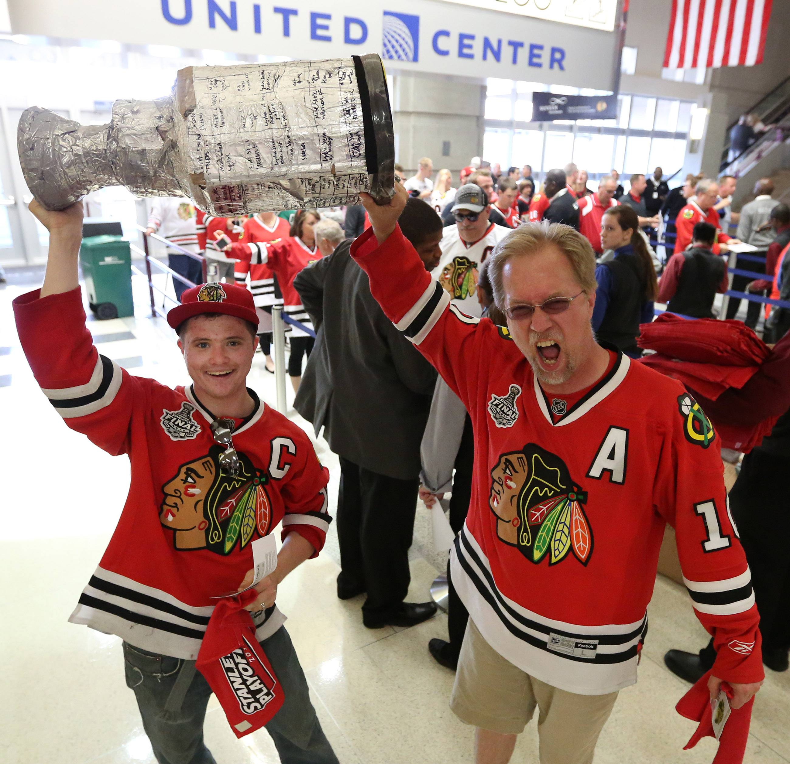 Mike Steele with his dad, Scott, both of Naperville enter the United Center with a Stanley Cup they made.