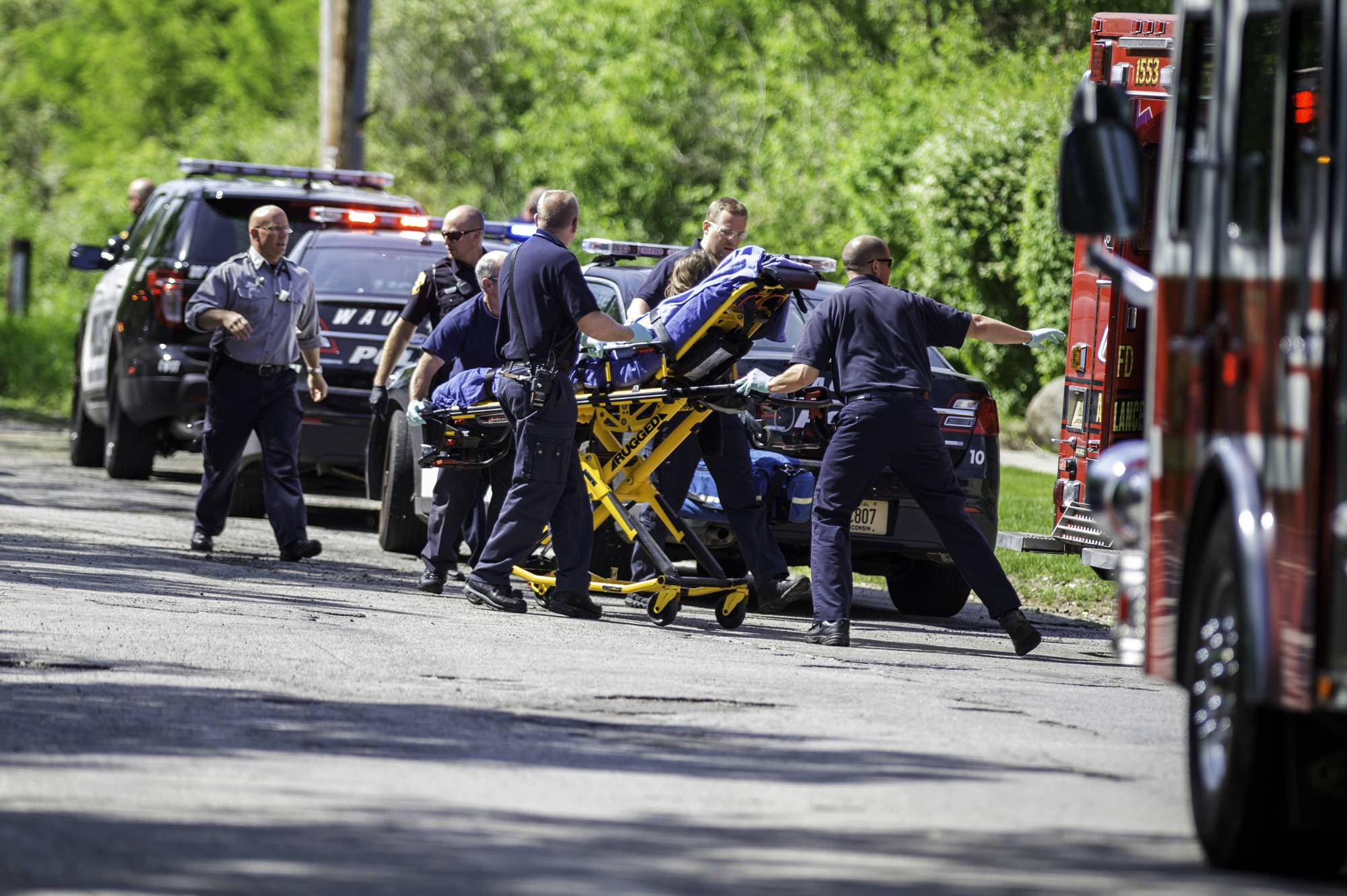 Rescue workers take a stabbing victim to the ambulance in Waukesha, Wis., Saturday. Prosecutors say two 12-year-old southeastern Wisconsin girls stabbed their 12-year-old friend nearly to death in the woods to please a mythological creature they learned about online.