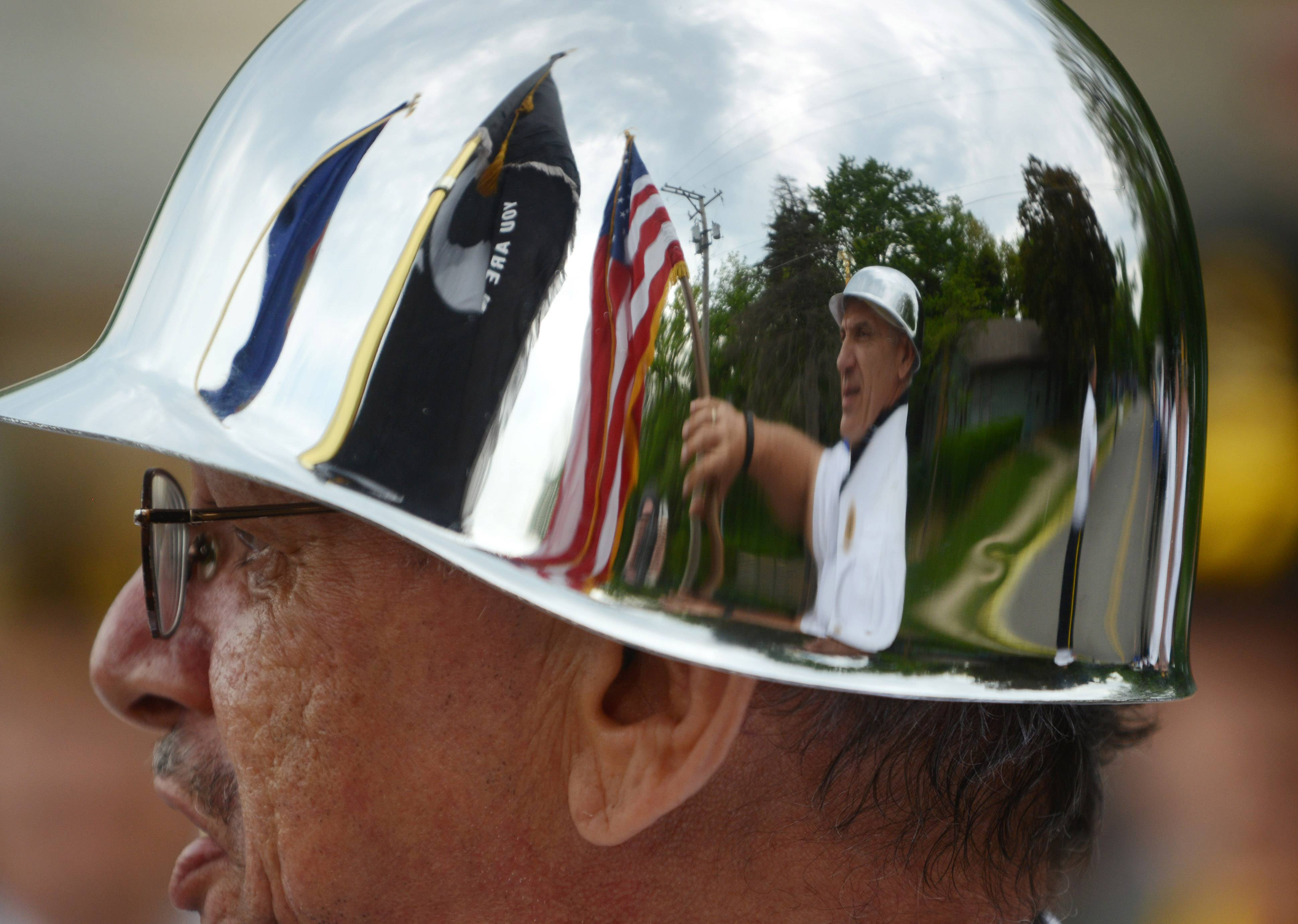 Paul Valade/pvalade@dailyherald.com Lake Zurich American Legion Post 964 member Paul Carrubba carries the American flag and is reflected in the helmet of fellow post member Angel Lebron during Monday's Memorial Day parade in Lake Zurich.