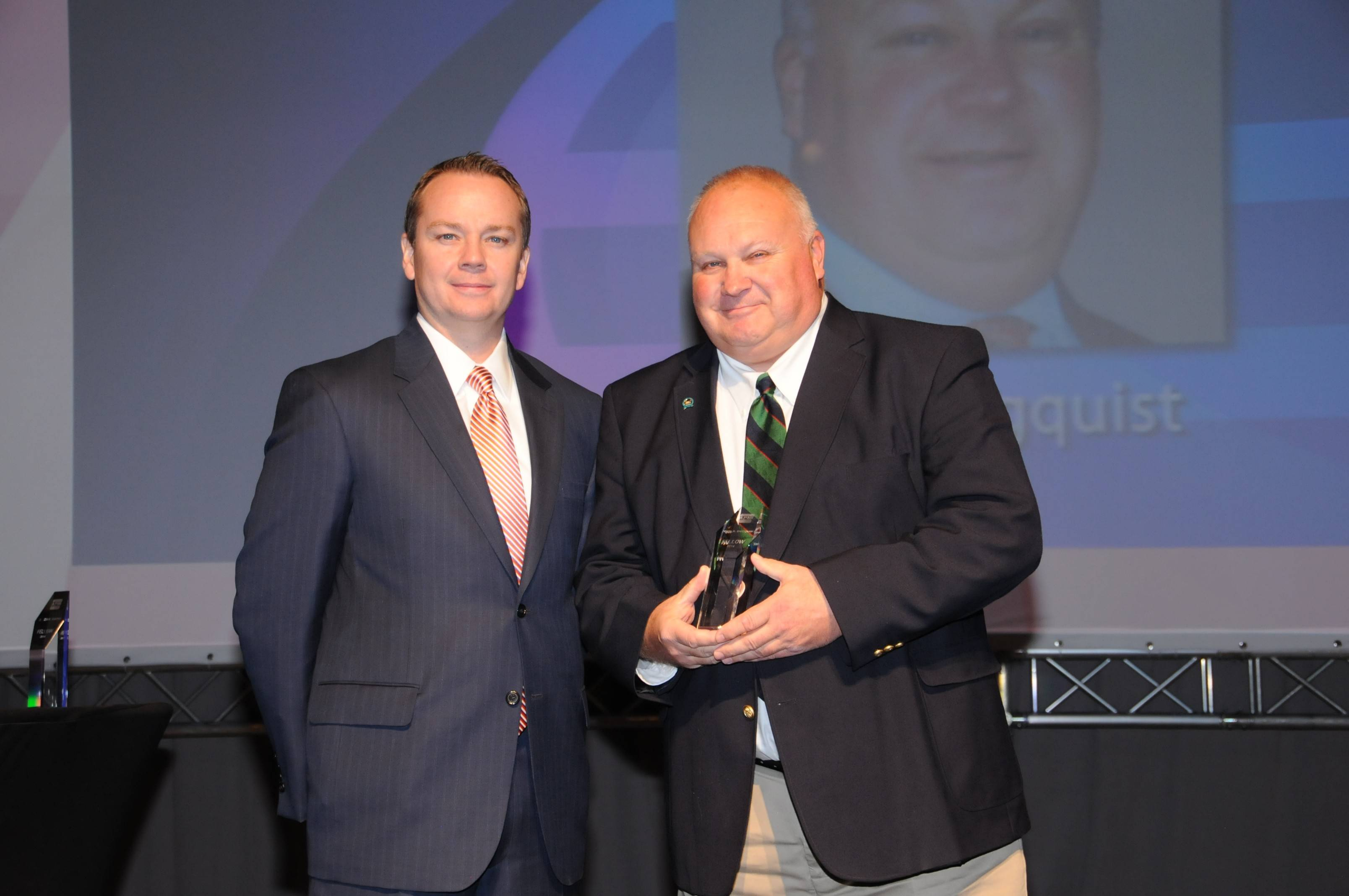John Engquist, right, receives an award from APMI President Dean Howard.