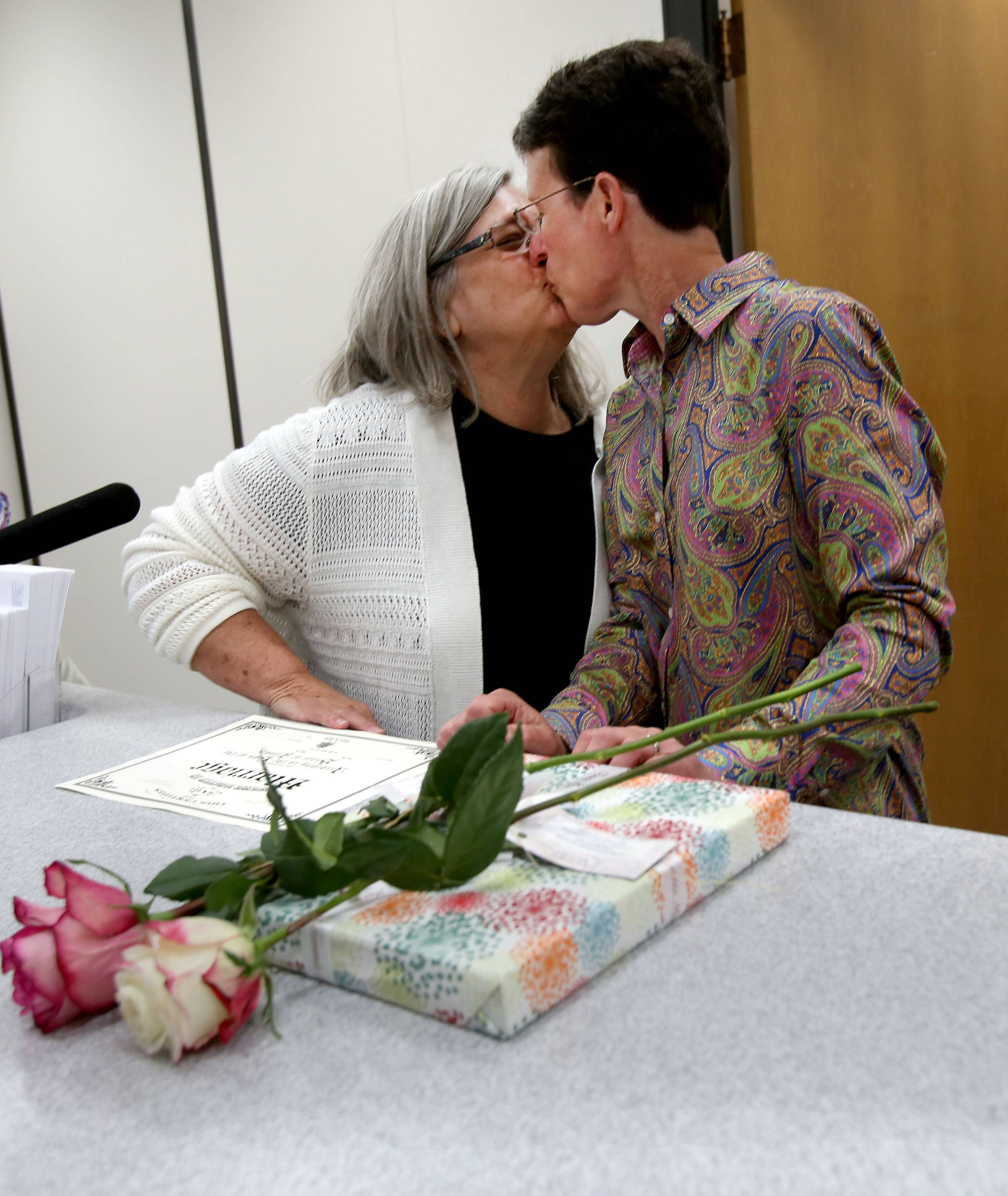 Barb McMillan, left, gives a kiss to her wife Roseann Szalkowski after they were able to convert their civil union to a marriage license at the DuPage County Clerk's office in Wheaton on Monday.  The couple from Roselle are now officially married since 2011.