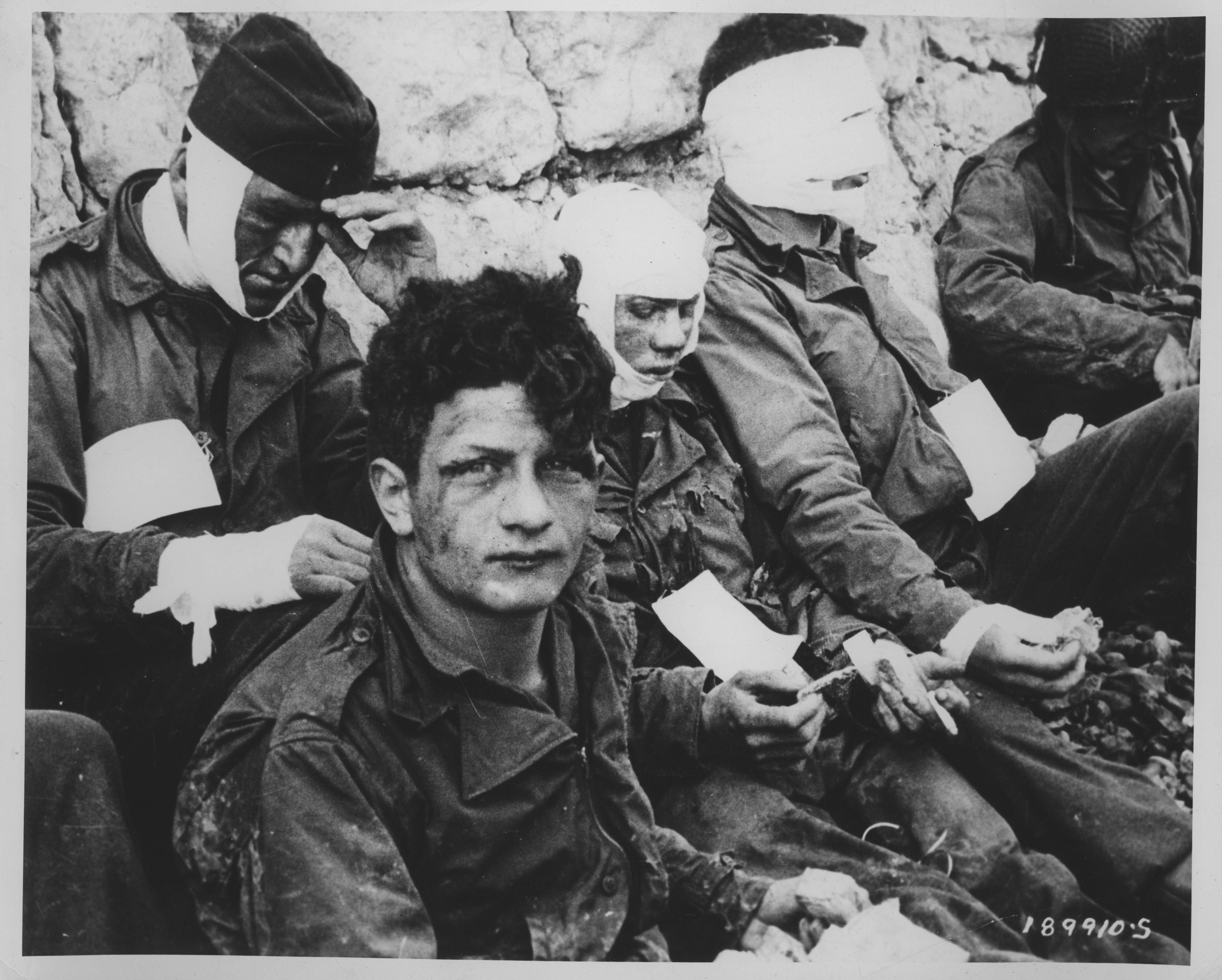 Assault troops of the 3rd Battalion, 16th Infantry, wounded on Omaha Beach, wait by the chalk cliffs for further medical treatment.