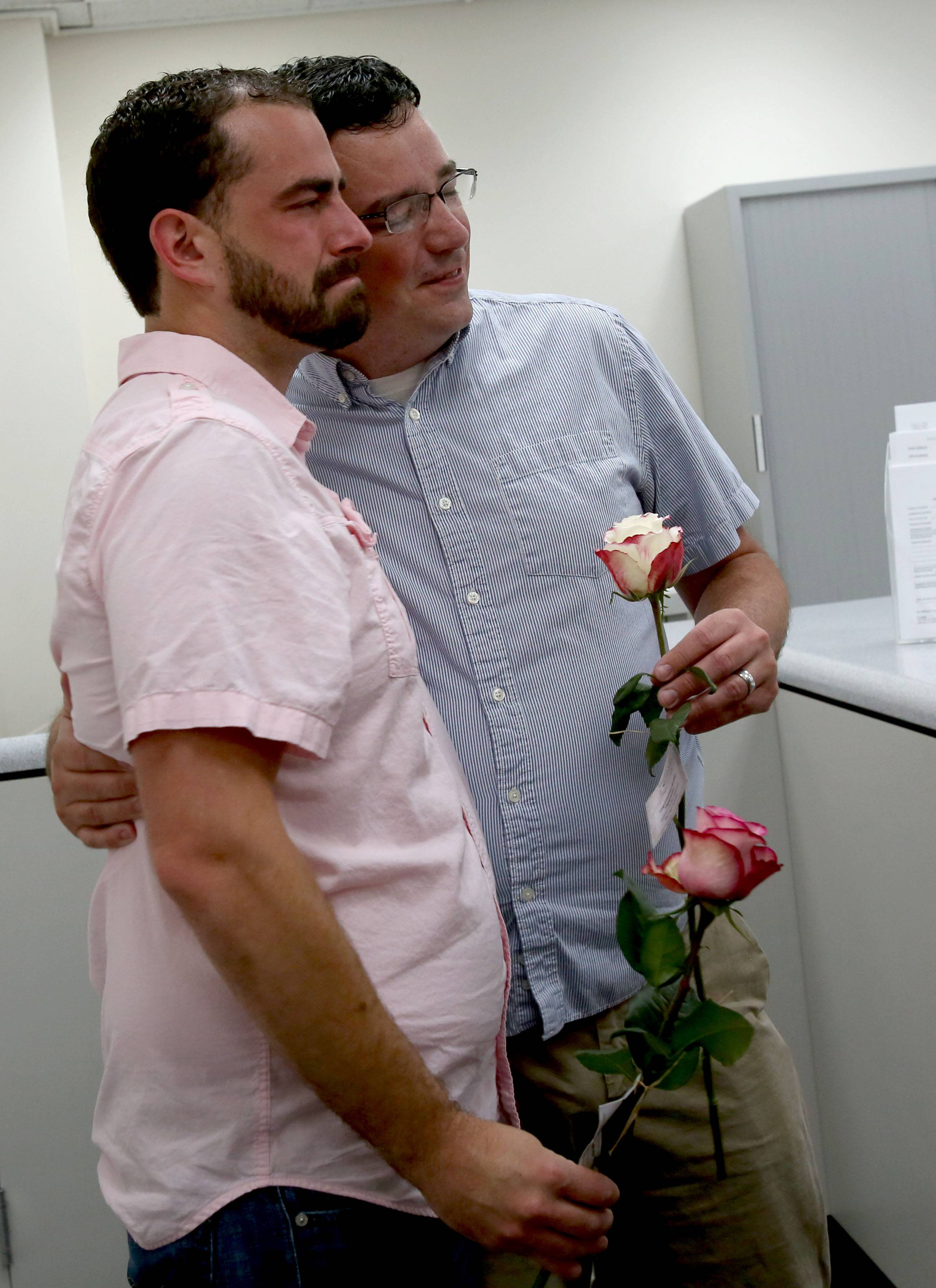 Mike Gary, left and Michael Cannon, right, of Hanover Park, share an emotional hug before converting their civil union to a marriage license Monday at the DuPage County Clerk's office in Wheaton.