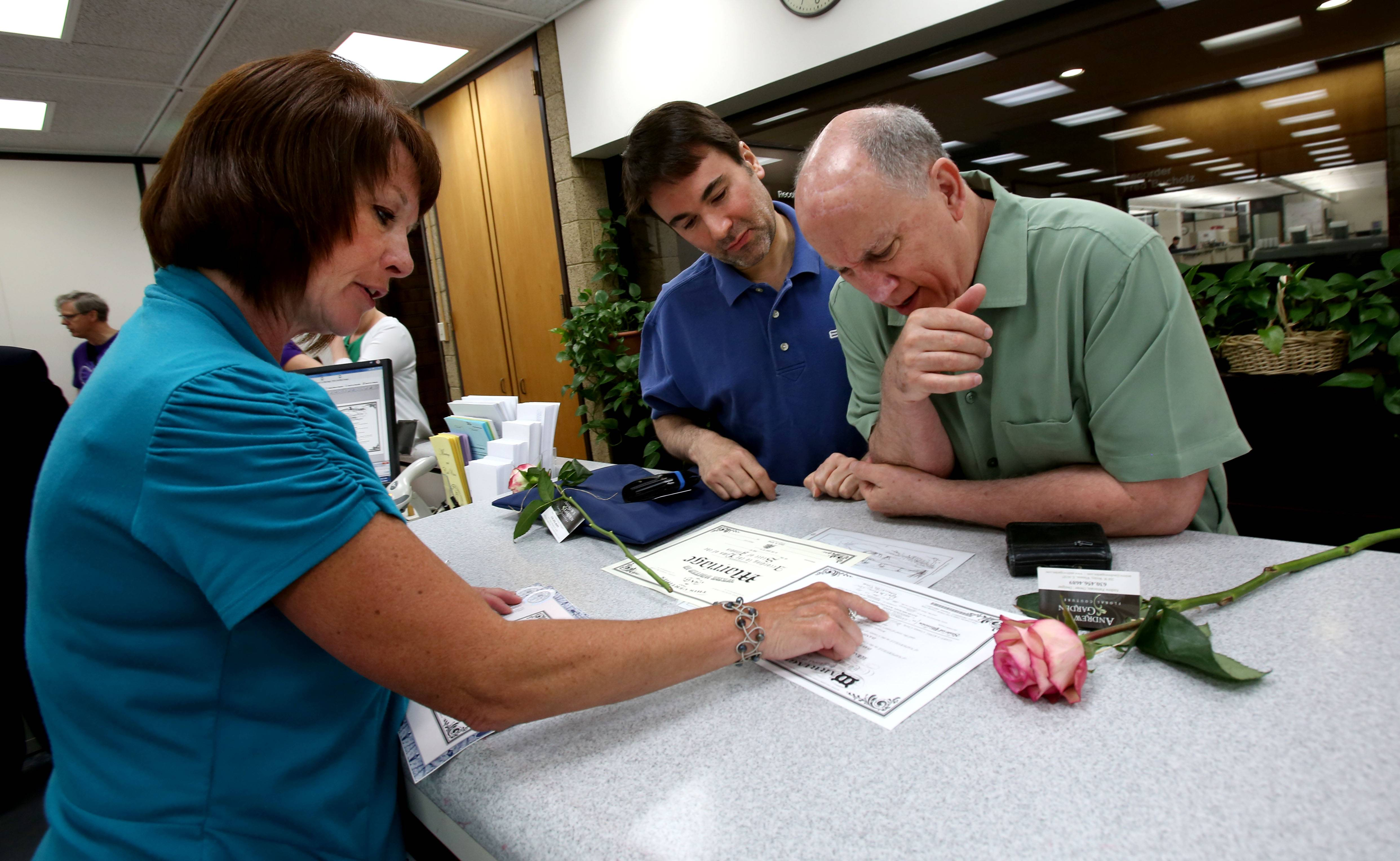 Shelley Bellock, left, deputy clerk, helps Naperville residents David Mancini-Conway, center, and Dan McGuire, right, with their marriage license Monday at the DuPage County Clerk's office in Wheaton. Same-sex marriage officially became legal in the state on Sunday.