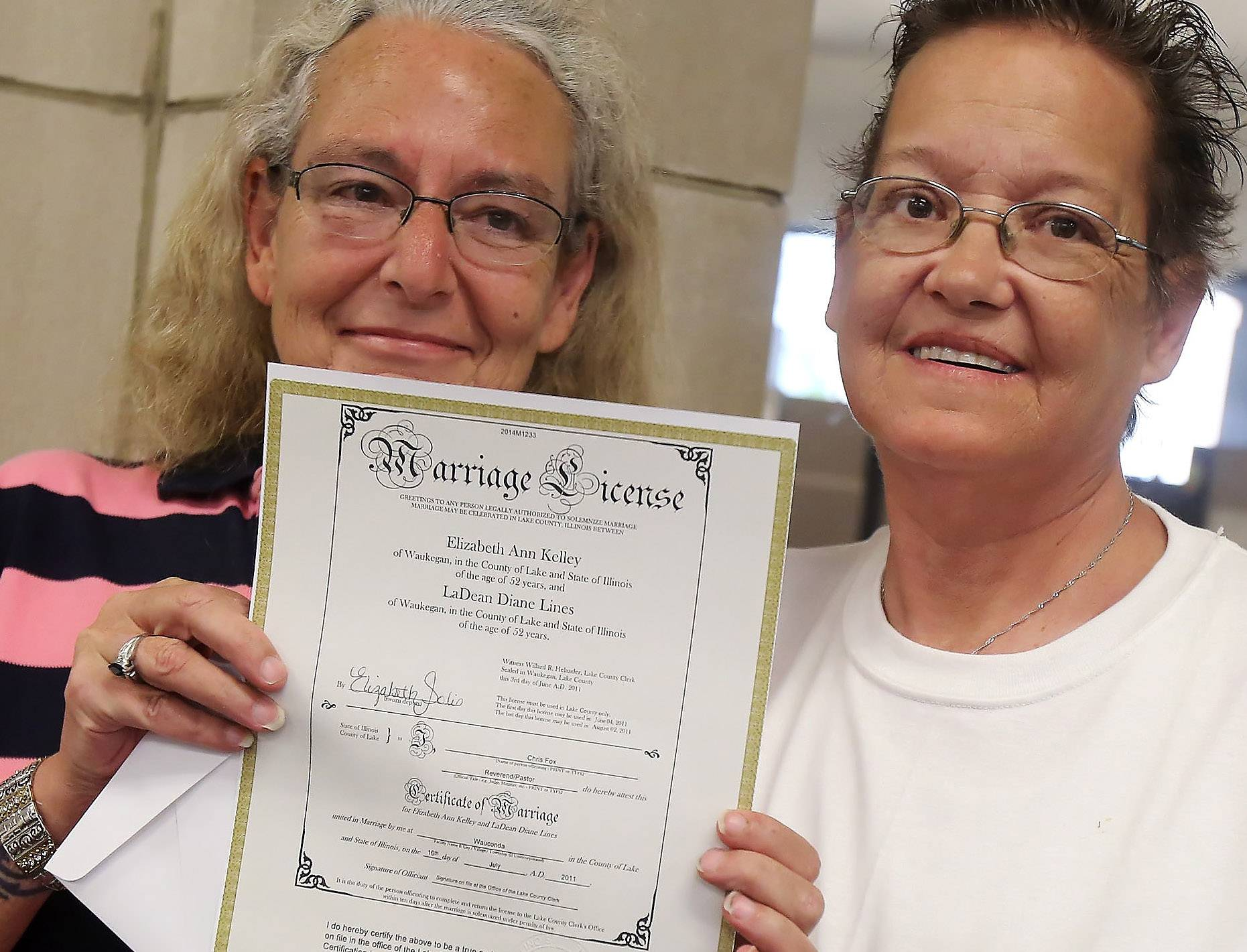LaDean Lines and Beth Kelley hold up their marriage license after being first in line as same-sex couples received marriage licenses Monday at the Lake County clerk's office in Waukegan. The law legalizing same-sex marriages in the state of Illinois became effective on Sunday.