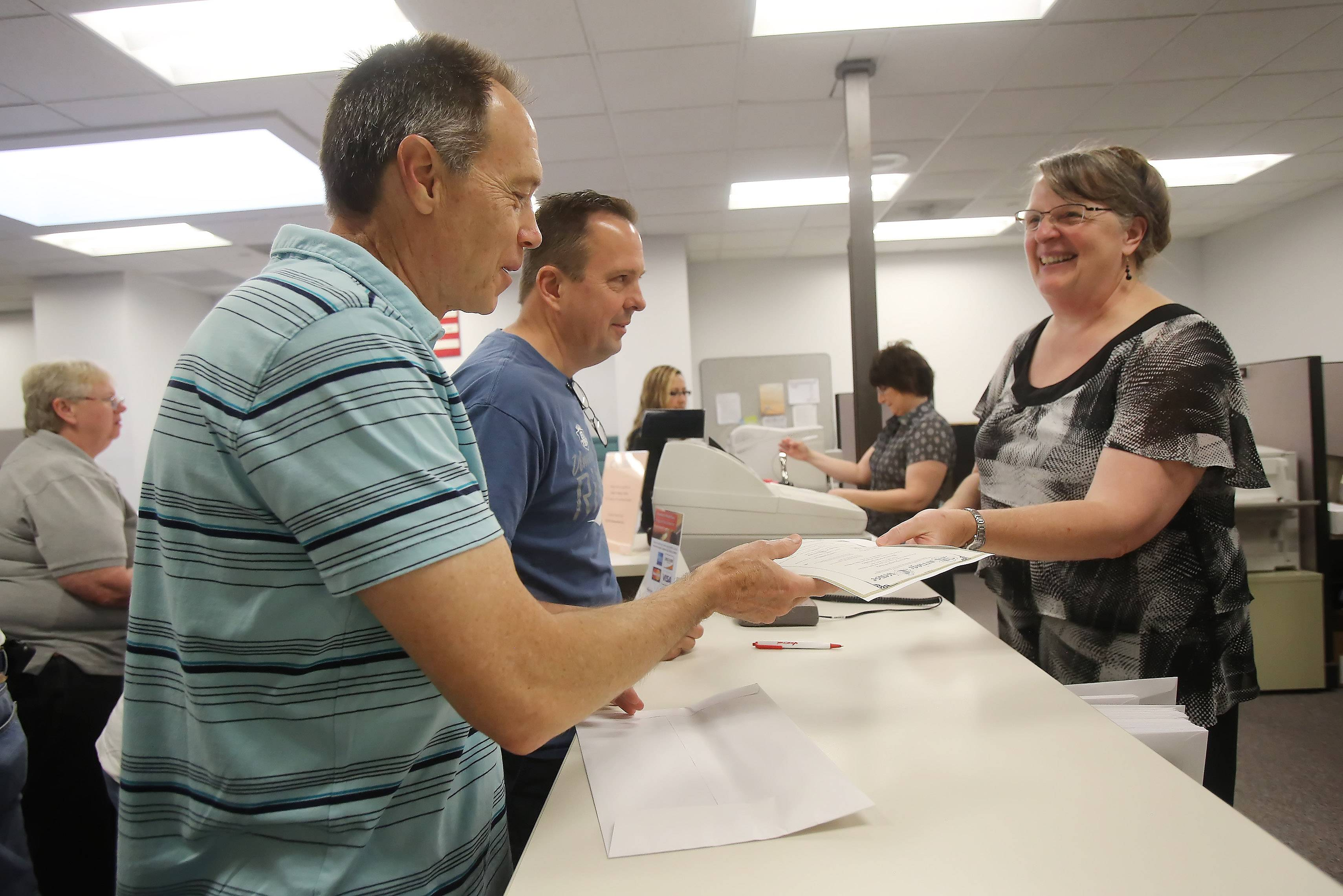 Kevin Schaller and Kevin Fulara of Wauconda receive a marriage license from Mary Anne Potter, of the Lake County clerk's office, as same-sex couples obtained licenses for the first time Monday. The law legalizing same-sex marriages in Illinois became effective on Sunday.