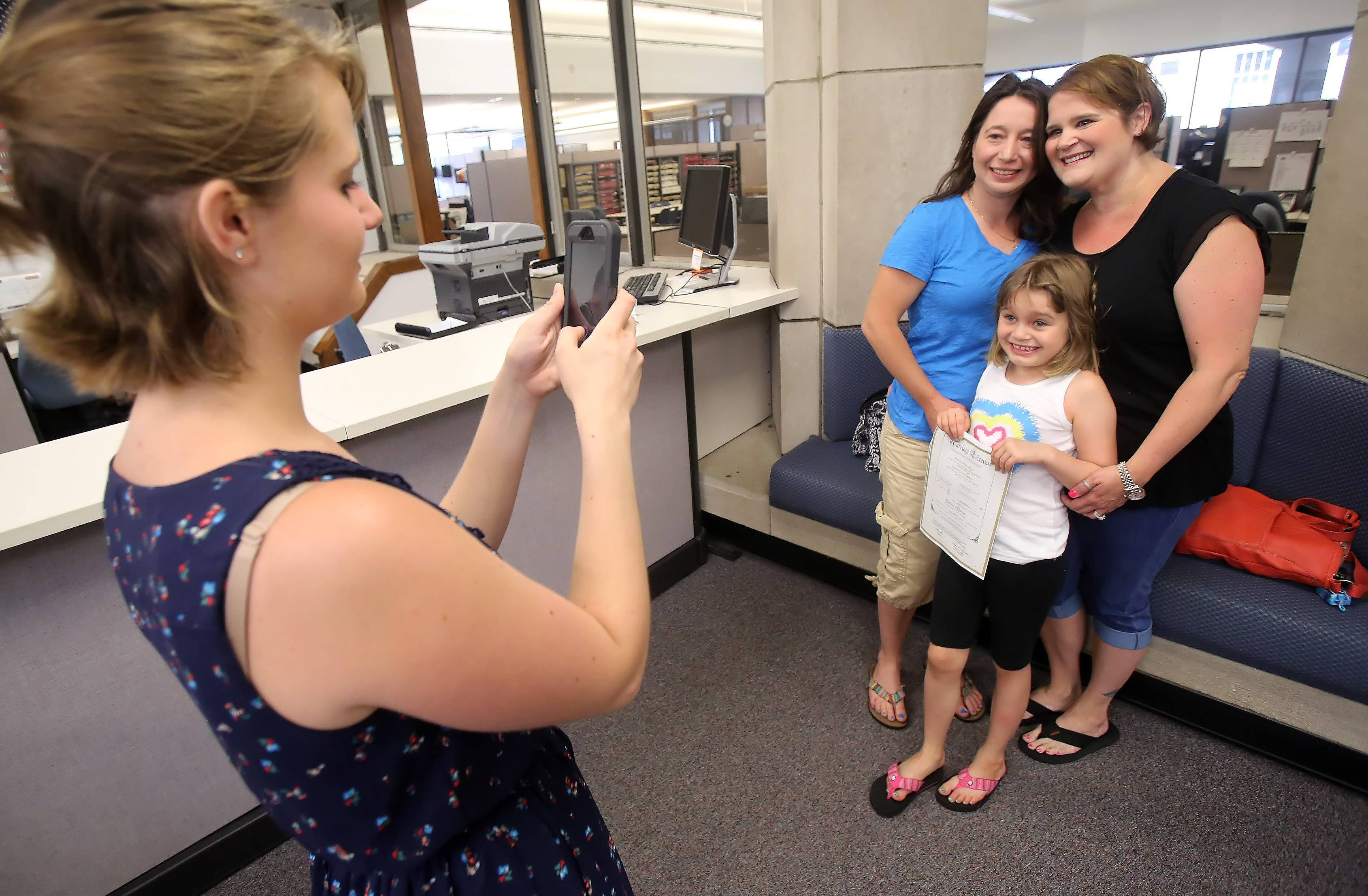 Kendall Welton of Round Lake Beach takes pictures of her sister, Michele Fagiano, right, with her partner, Shannon, and their daughter, Riley, 7, after receiving a marriage license Monday at the Lake County clerk's office in Waukegan. The law legalizing same-sex marriages in Illinois became effective on Sunday.