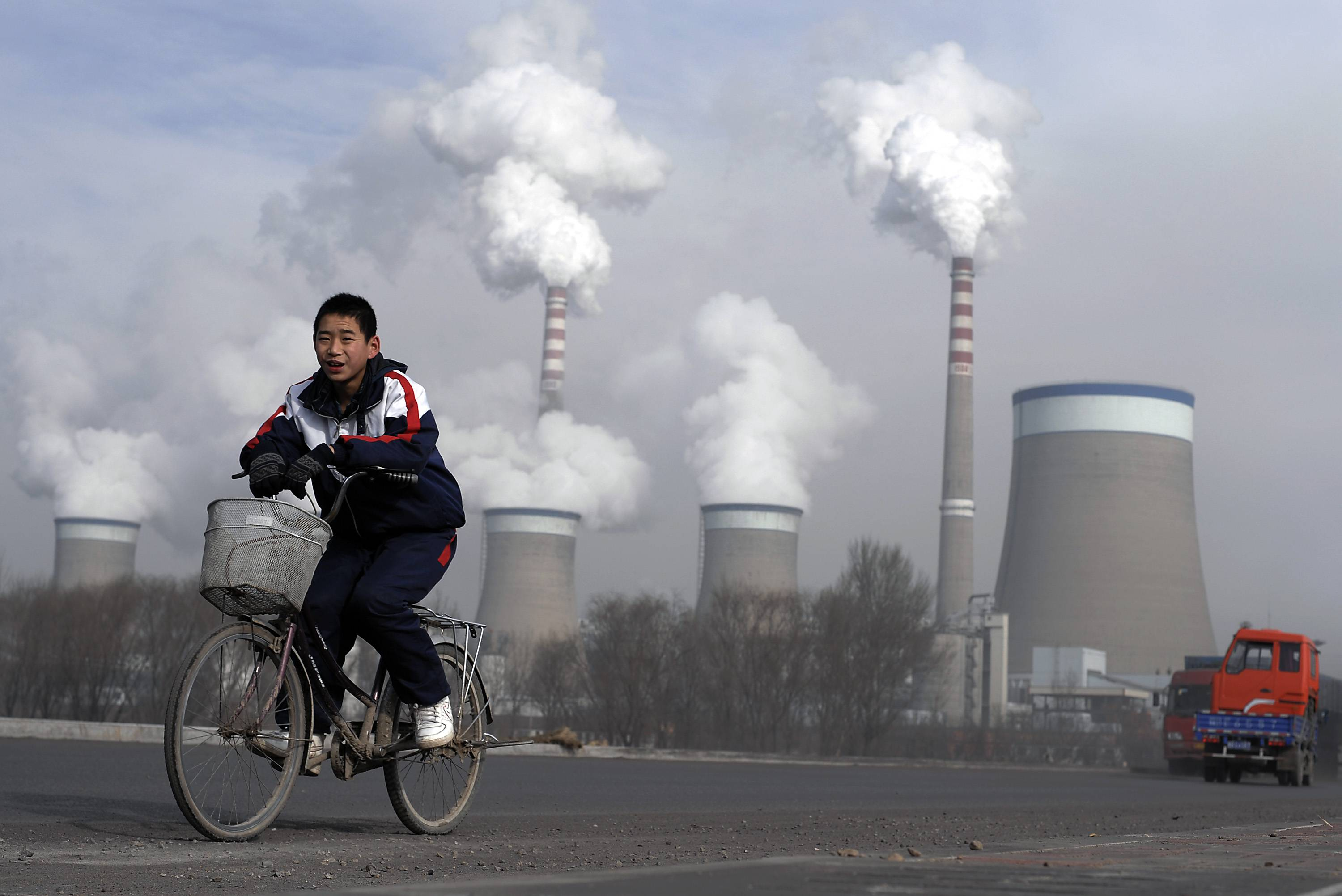 A boy cycles past cooling towers of a coal-fired power plant in Dadong, Shanxi province, China. China, the biggest emitter of greenhouse gases, has promised to curb its output but with its economy slowing and leaders under pressure to generate jobs, it has resisted binding limits.