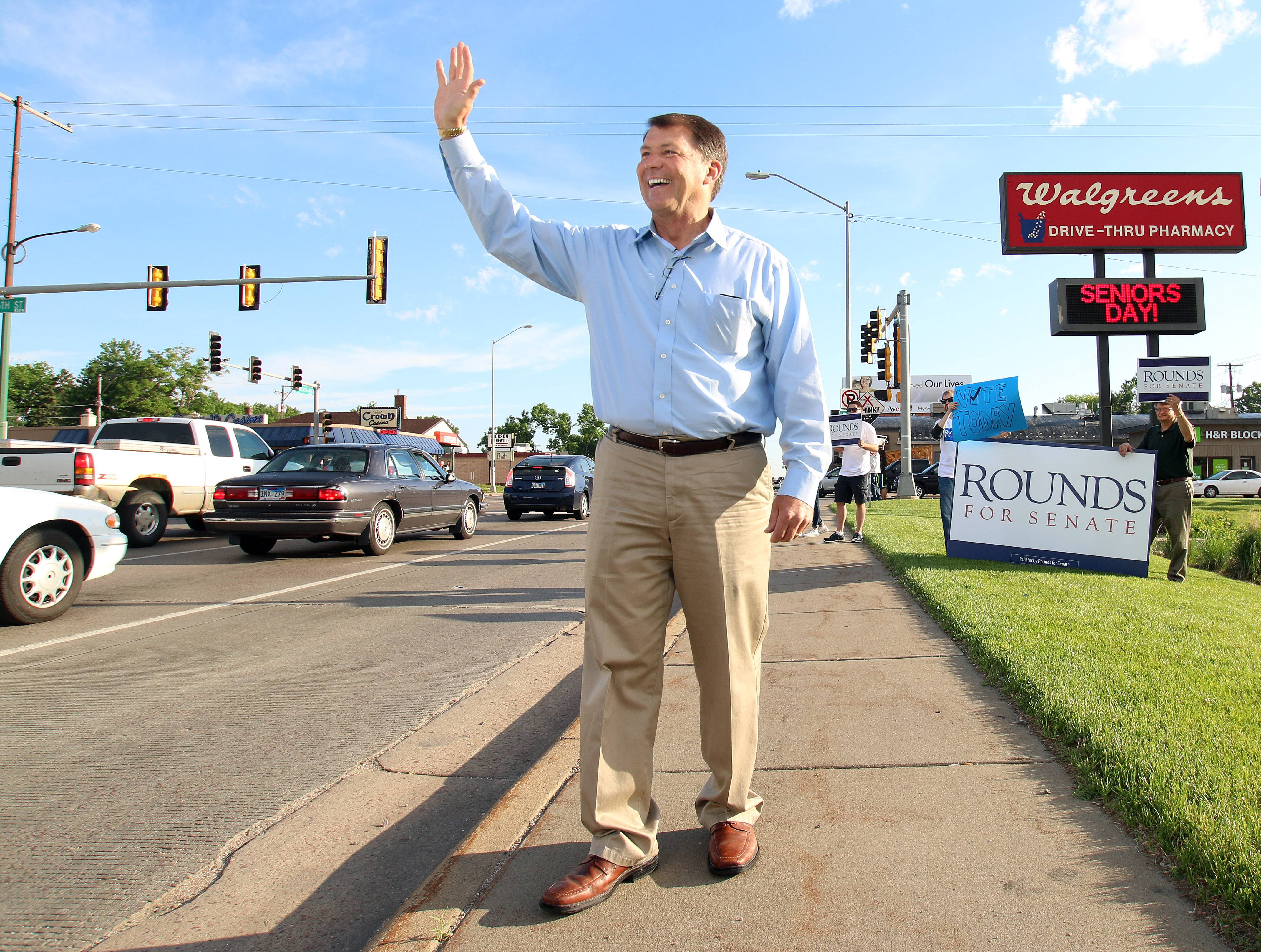 Former South Dakota Gov. Mike Rounds waves to motorists, as he campaigned Tuesday in Sioux Falls, S.D. Rounds won the Republican nomination for the U.S. Senate — and instantly became the favorite to pick up a seat for the GOP in its drive to capture a majority this fall.