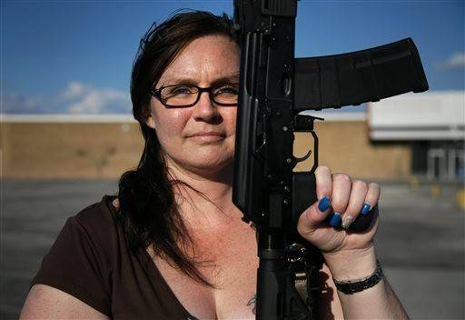 Tara Cowan of Euless, Texas, a member of Open Carry Tarrant County, poses for a portrait with a Saiga 556 rifle as she and members of the group Open Carry Tarrant County gathered for a demonstration, Thursday, May 29, 2014, in Haltom City, Texas.