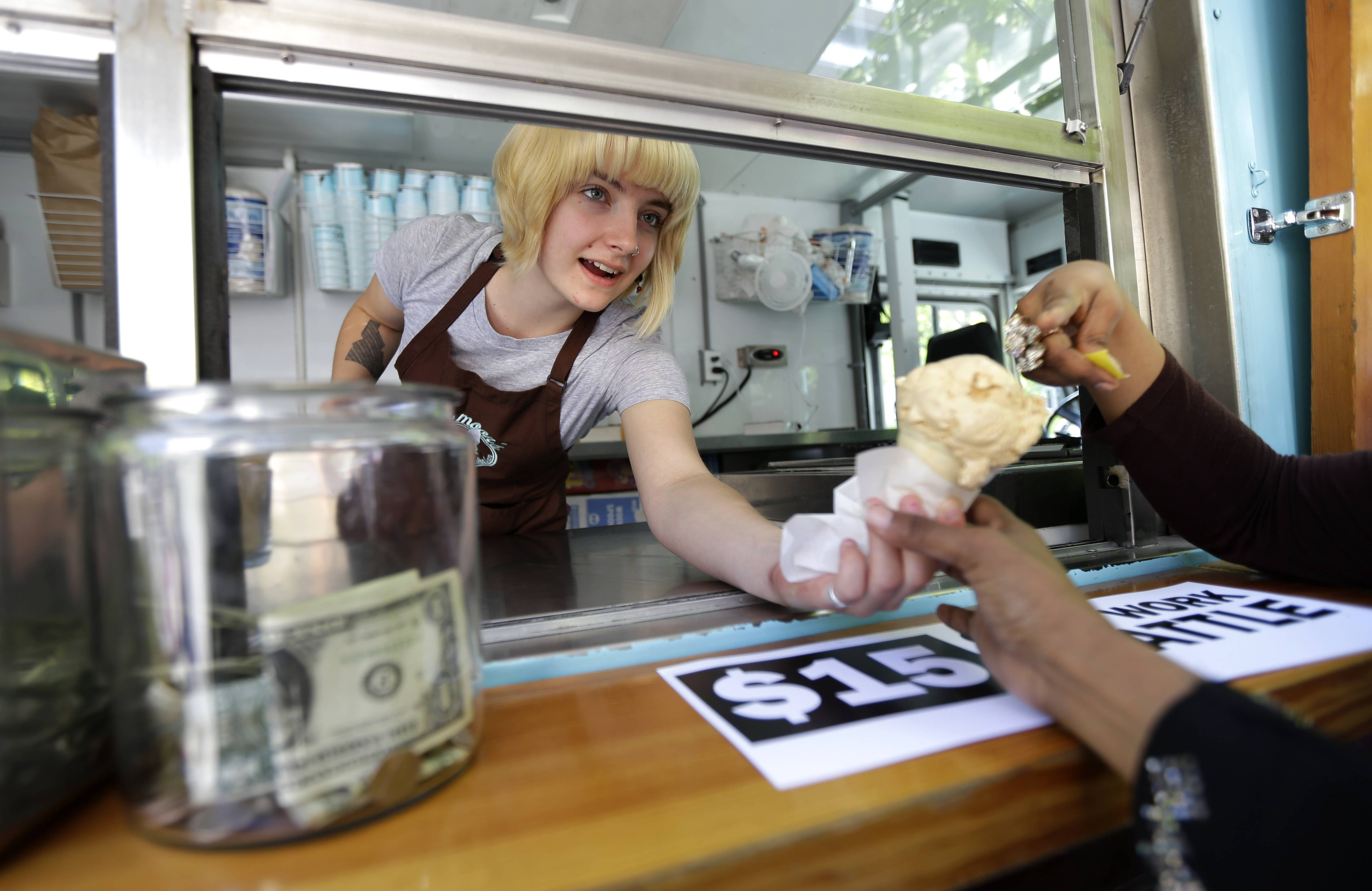 Caitlyn Faircloth, a worker with Molly Moon's Homemade Ice Cream, hands out free ice cream next to a tip jar, Monday, June 2, 2014, at a rally celebrating the passage of a $15 minimum wage measure outside Seattle City Hall in Seattle.