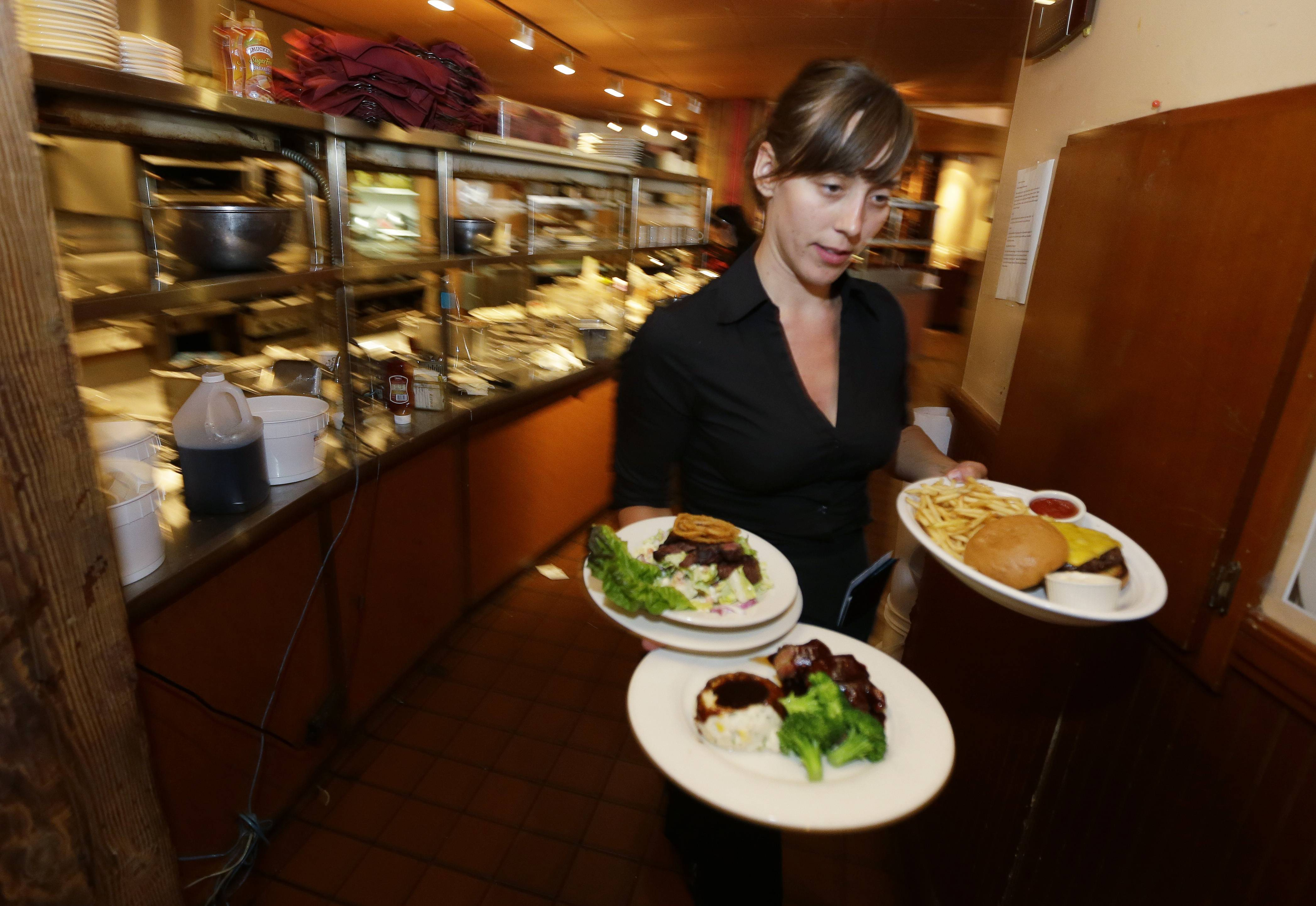 Wendy Harrison, a waitress at the Grill in Seattle, carries food to a table as she works during lunchtime. An Associated Press comparison of the cost of living at several other major U.S. cities found that a $15 minimum wage, like Seattle adopted this week, will make a difference, but won't buy a lavish lifestyle.