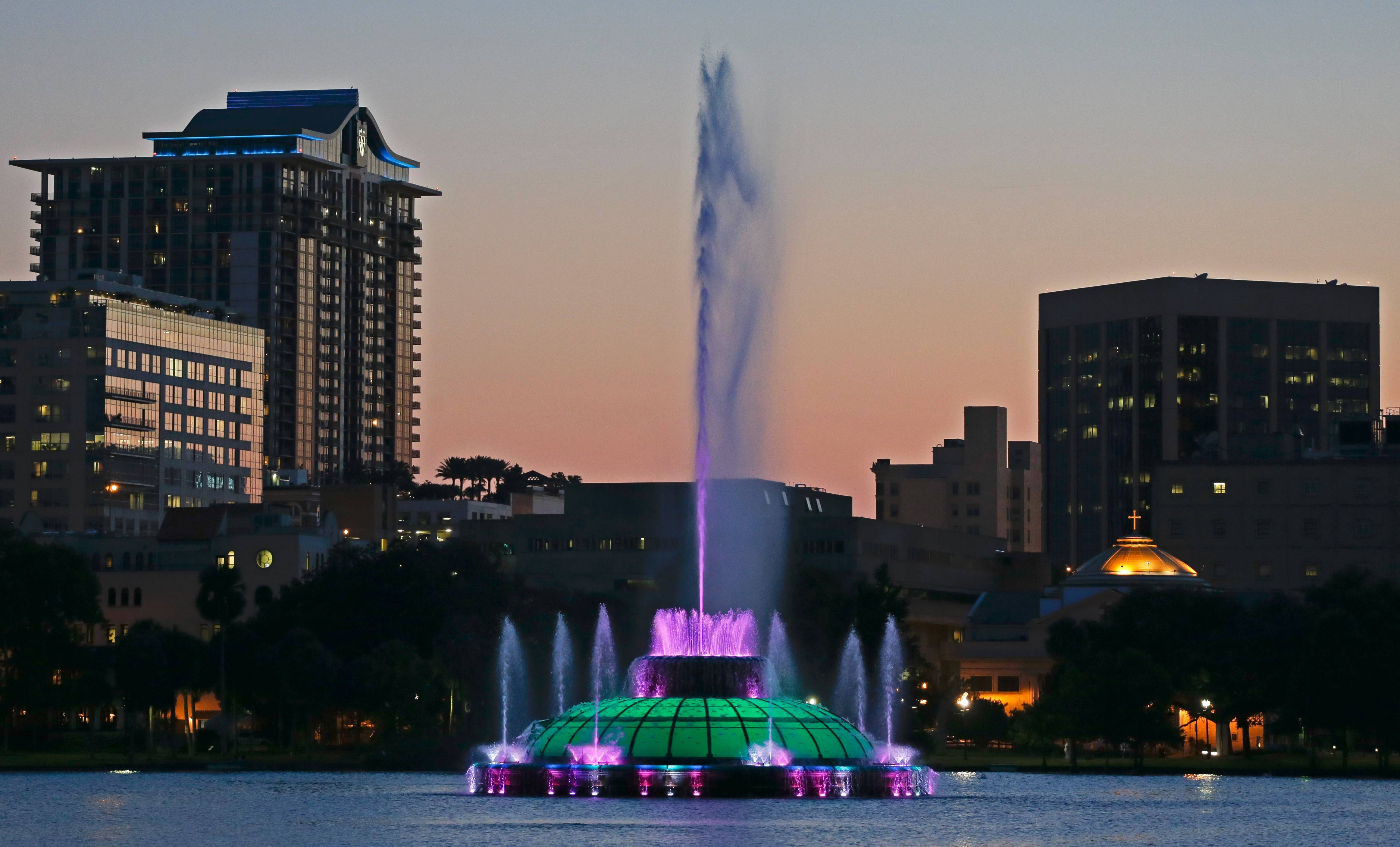 Water rises from a five-decade-old, green, multitiered fountain on Lake Eola that is the official icon of the city as the sun sets in Orlando, Fla. Every night, passers-by are treated to a six-minute water show from the fountain featuring multicolored bursts of water timed to music.