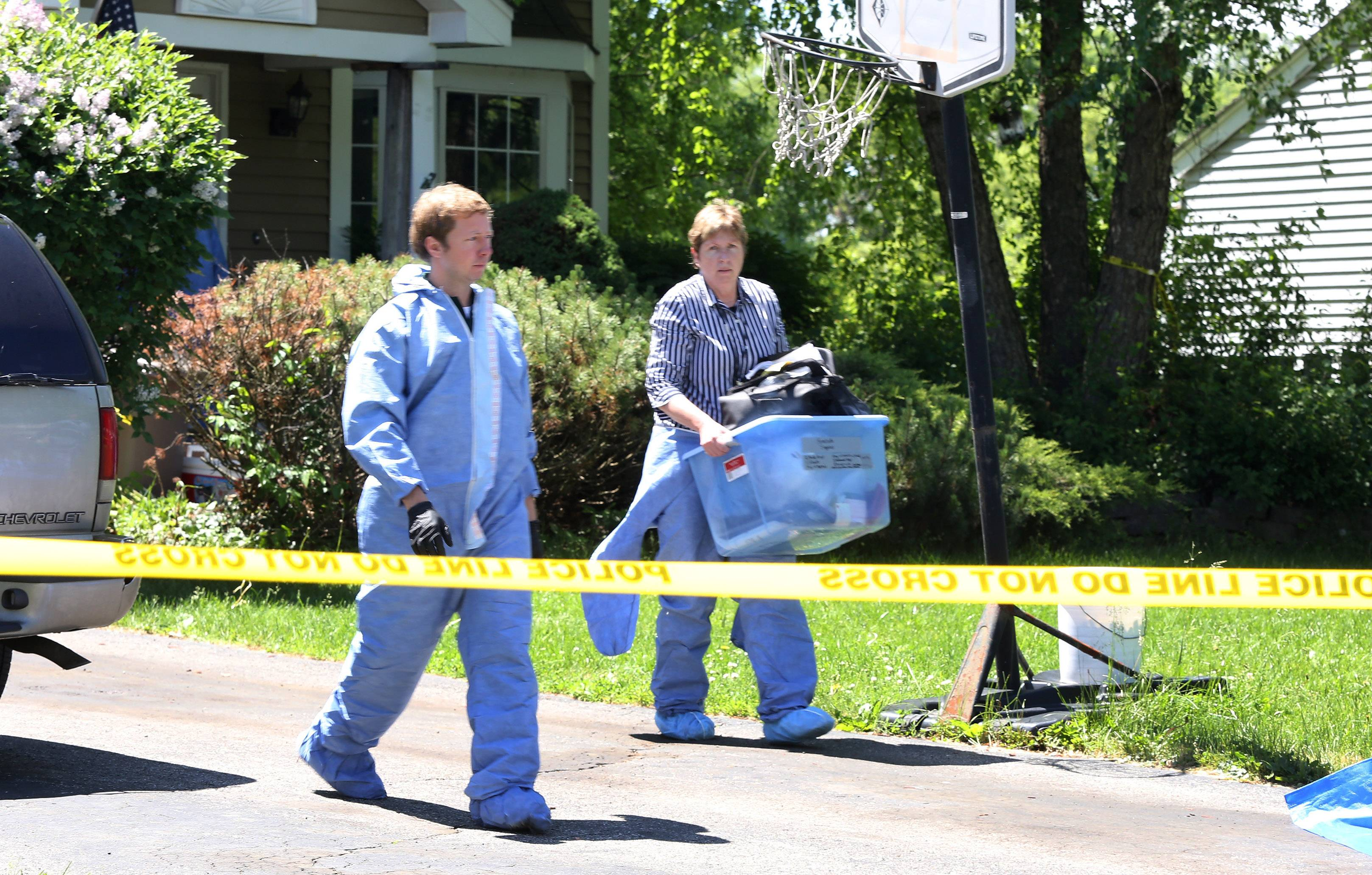 Police leave a house on Dartmouth Drive on Tuesday.