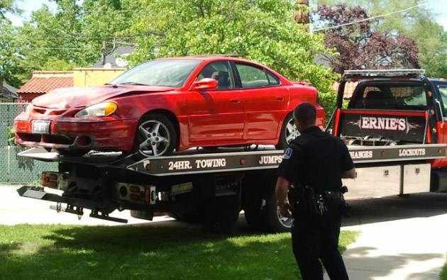 Mundelein police watch as the car that crashed into a house on Diamond Lake Road is towed away.