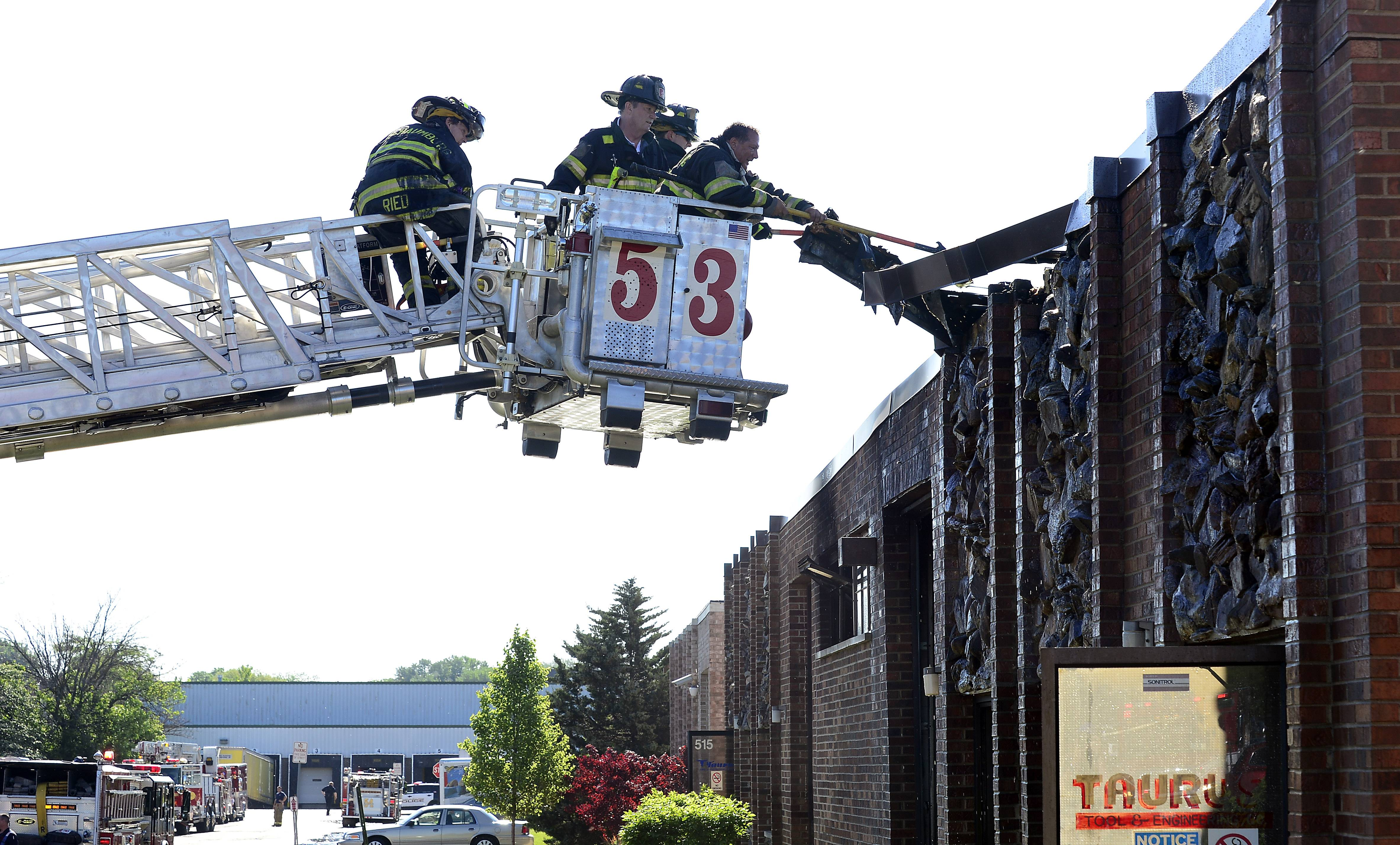 Schaumburg firefighters use the aerial ladder Tuesday morning to rip away at the facade of the Taurus Tool and Engineering Inc. on the 500 block of Estes Avenue in Schaumburg after fire broke out.