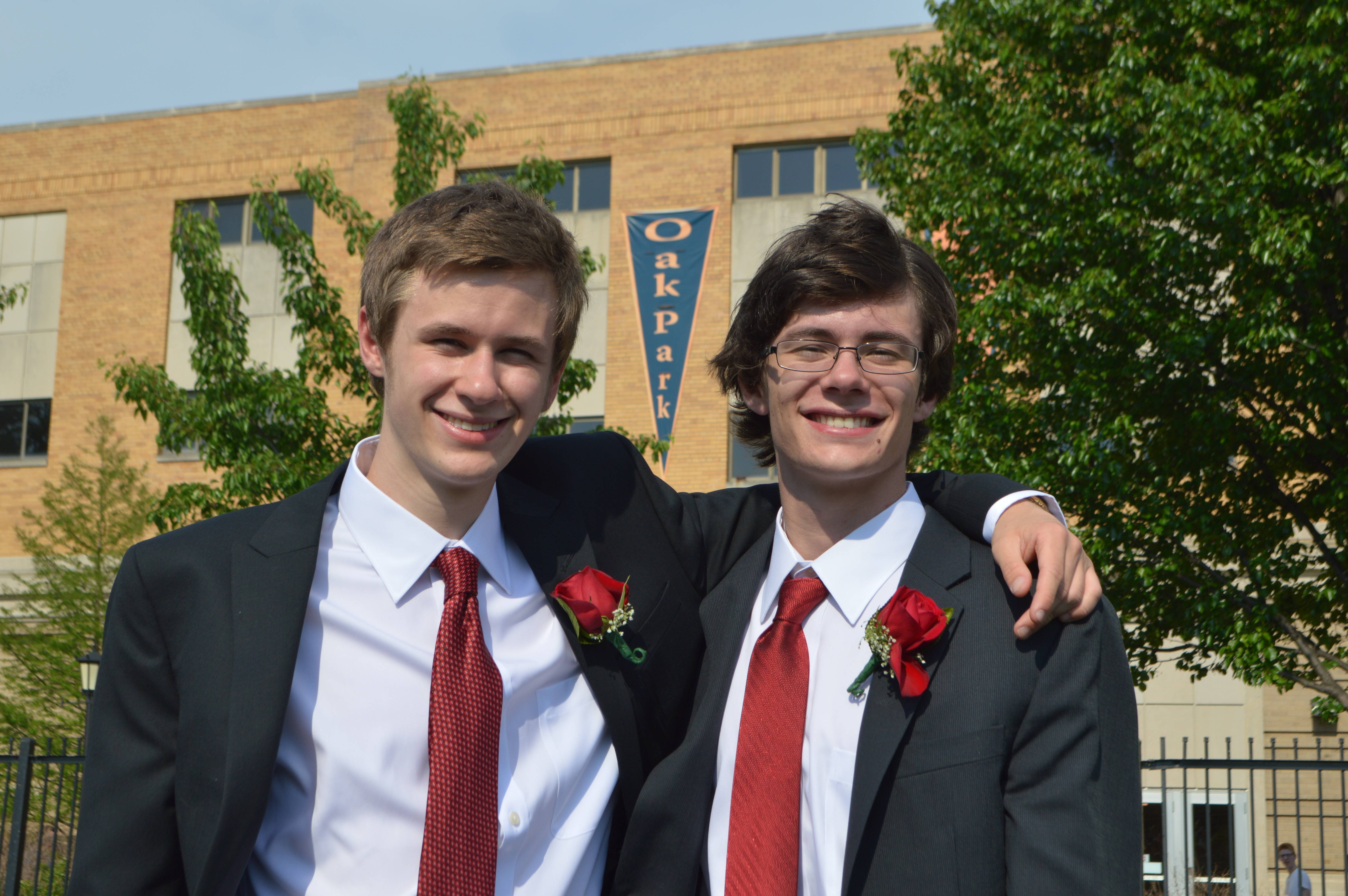 On the stadium field after their commencement, high school graduates Ross, left, and Ben Constable acquiesce to their parents' request for a photograph. Tradition at their school requires suits instead of caps and gowns.