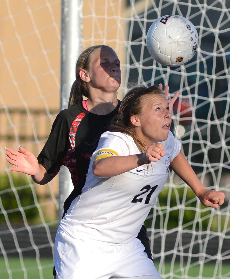 St. Charles East's Amanda Hilton heads the ball in front of Huntley's Abigail Nordeen in the second half of the Class 3A girls soccer supersectional at Lake Park High School in Roselle on Tuesday, June 3.