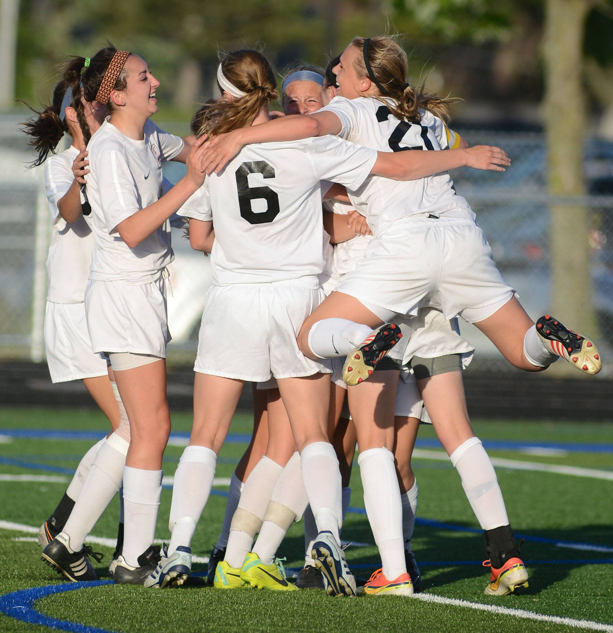 St. Charles East's Amanda Hilton leaps onto her teammates as they celebrate Rion Gaffney's goal in the second half over Huntley in the Class 3A girls soccer supersectional at Lake Park High School in Roselle on Tuesday, June 3.