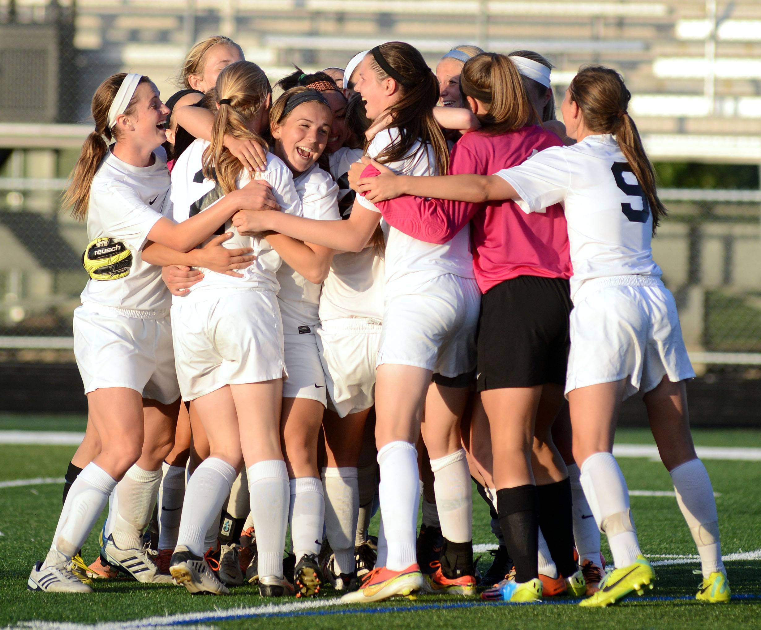 St. Charles East's Anna Corirosi (facing) and teammates embrace on the field after their 2-0 win over Huntley in the Class 3A girls soccer supersectional at Lake Park High School in Roselle on Tuesday, June 3.