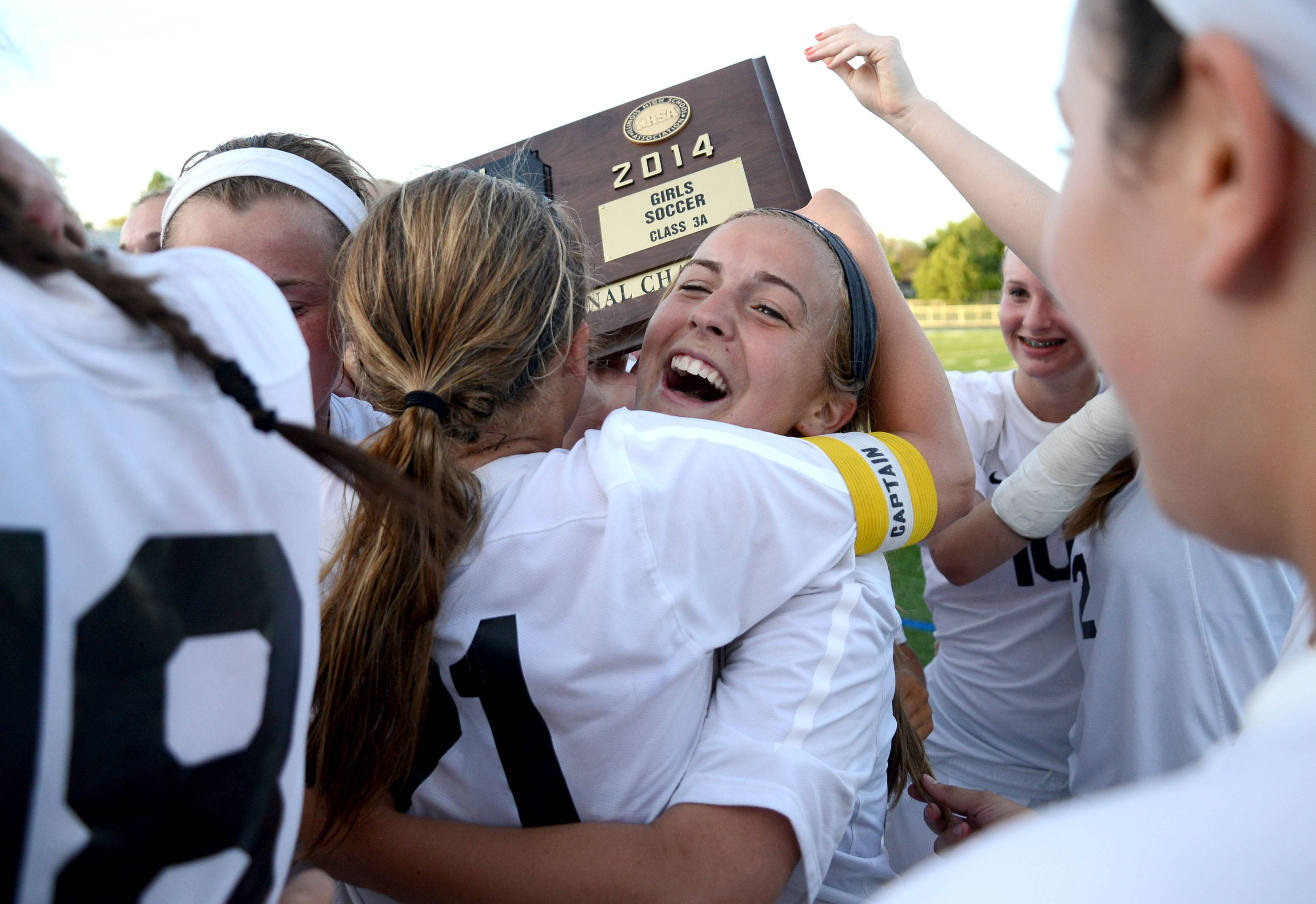 St. Charles East's Anna Corirosi (facing) and Amanda Hilton embrace after accepting their Class 3A girls soccer supersectional plaque at Lake Park High School in Roselle on Tuesday, June 3.