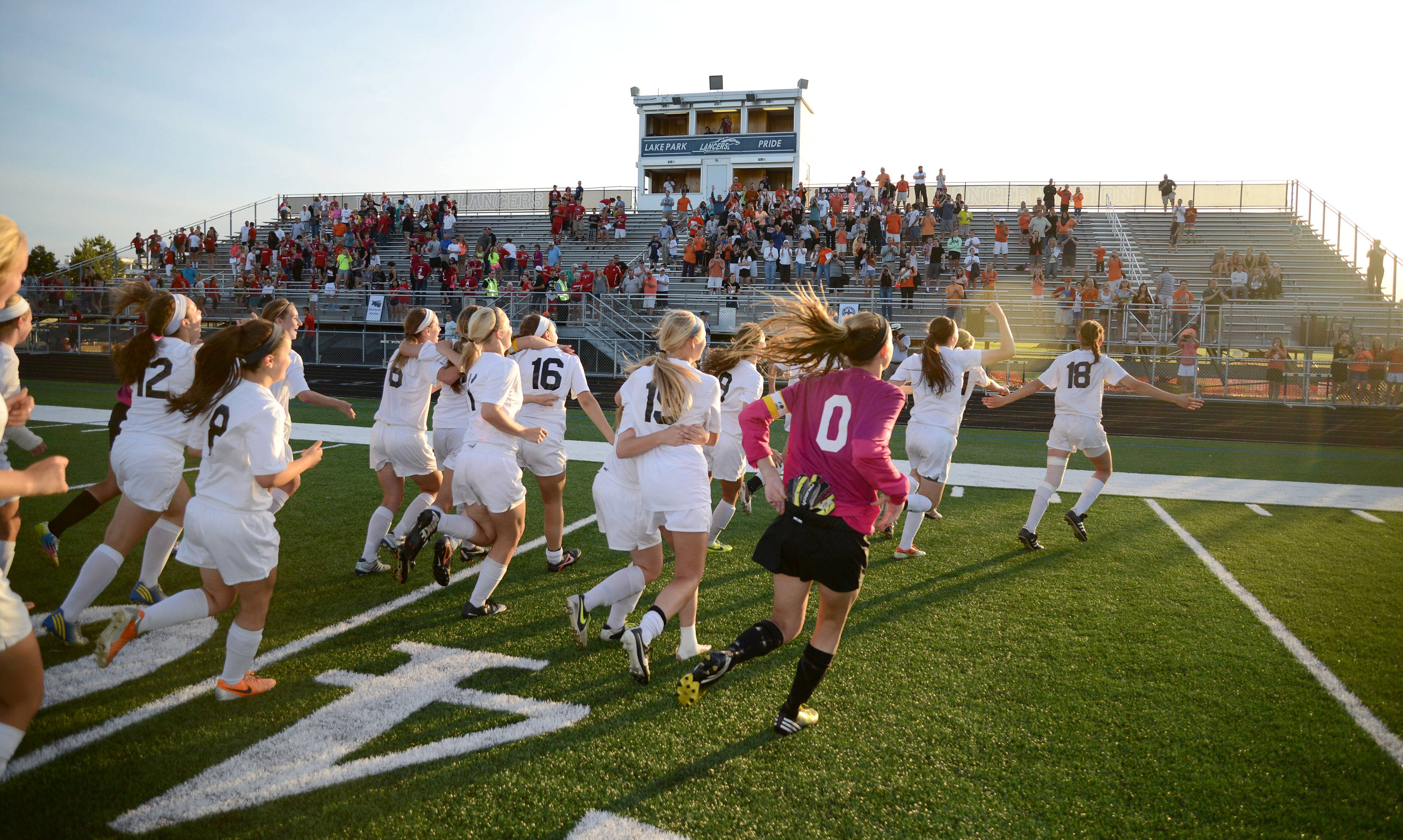 St. Charles East runs to fans in the bleachers after their the Class 3A girls soccer supersectional win over Huntley at Lake Park High School in Roselle on Tuesday, June 3.
