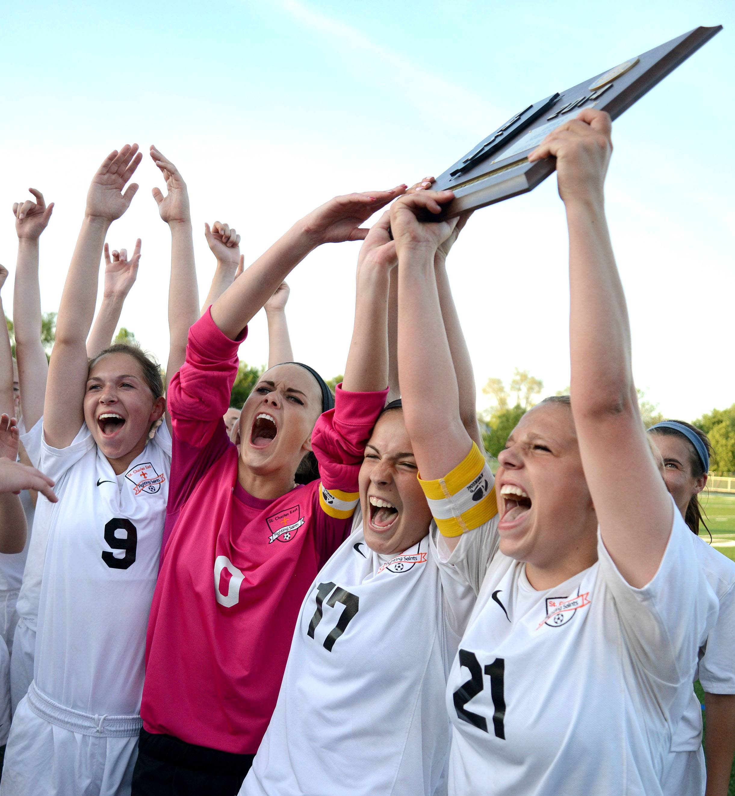 St. Charles East's Darcy Cunningham (9), Kendra Sheehan (0), Anna Corirosi (17) and Amanda Hilton (21) scream as they present their Class 3A girls soccer supersectional plaque to the crowd after their win over Huntley at Lake Park High School in Roselle on Tuesday, June 3.
