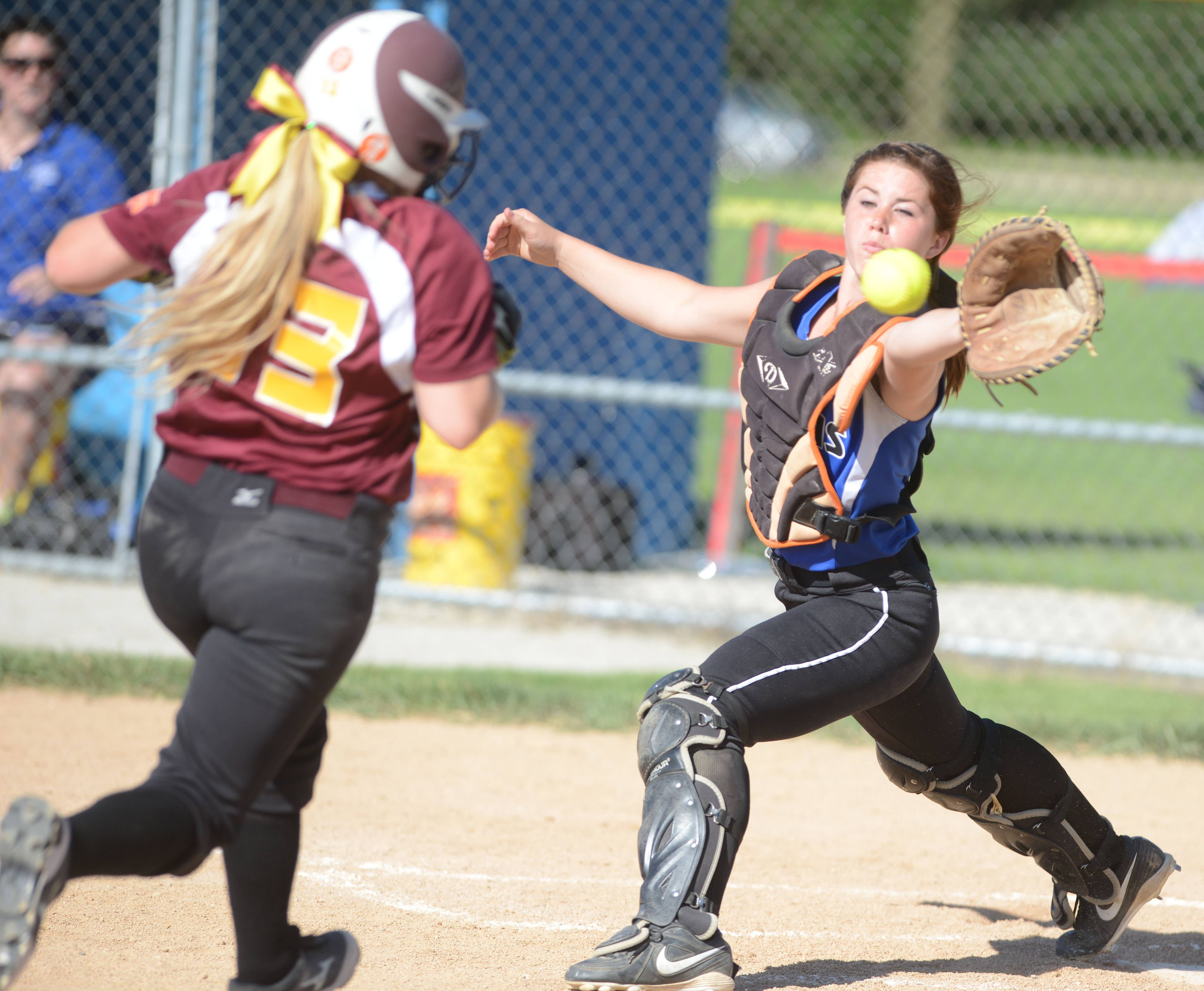 Amy Bukovsky (13) of Montini makes it home as Fiona Summers (4) of St. Francis reaches for the ball in the Class 3A Glenbard South sectional semifinals Tuesday.