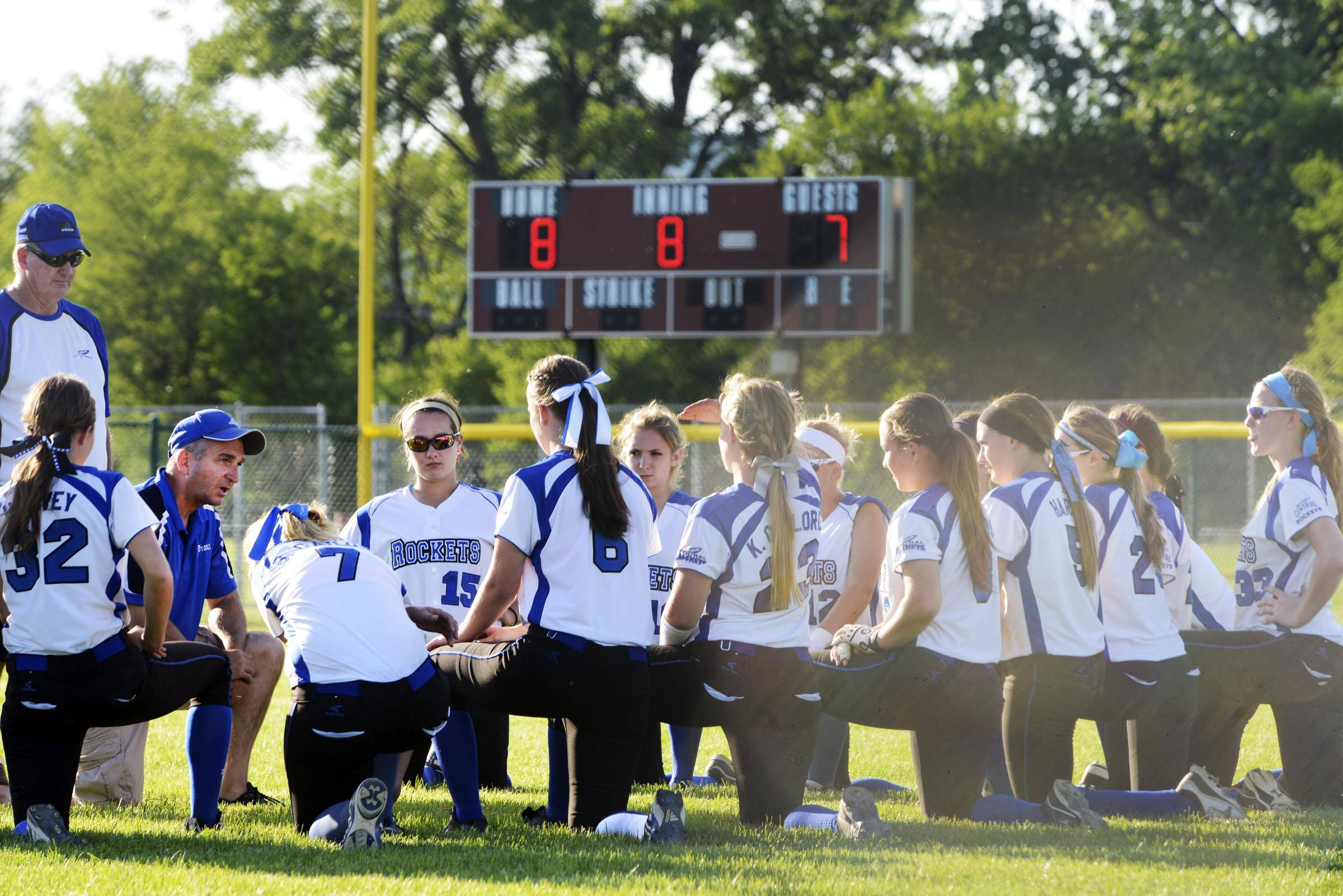 Burlington Central head coach Wade Maisto, kneeling at far left, meets with his team in the outfield under the scoreboard that shows their loss to Sterling Tuesday in the Class 3A Marengo sectional semifinal game. Maisto is stepping down as the Rockets' coach.
